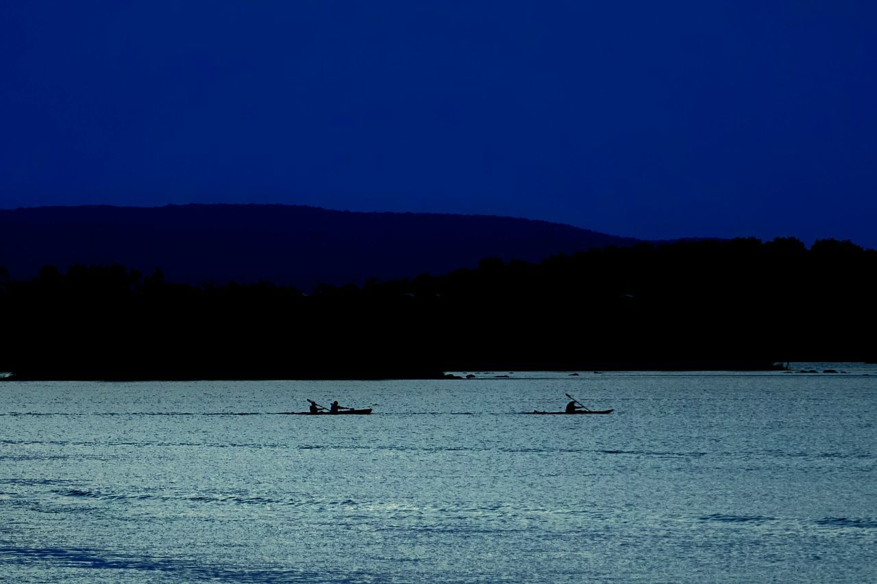 Silhouette People In Rowboat Over Montreal Lake Against Sky At Night