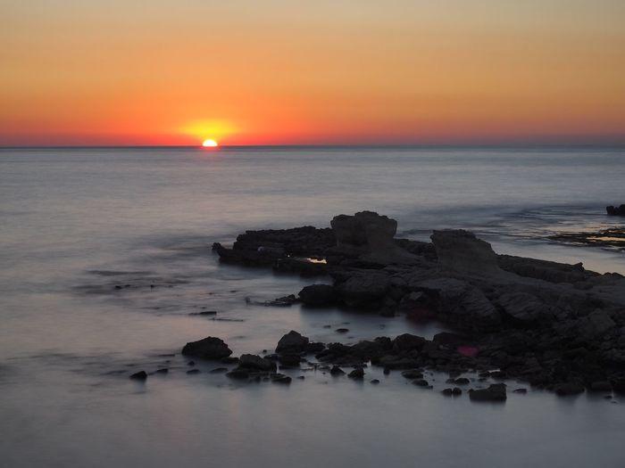 Sunset Sea Beauty In Nature Scenics Horizon Over Water Tranquil Scene Nature Water Tranquility Orange Color Sky Idyllic Beach Rock - Object Sun Outdoors No People Travel Destinations cyprus