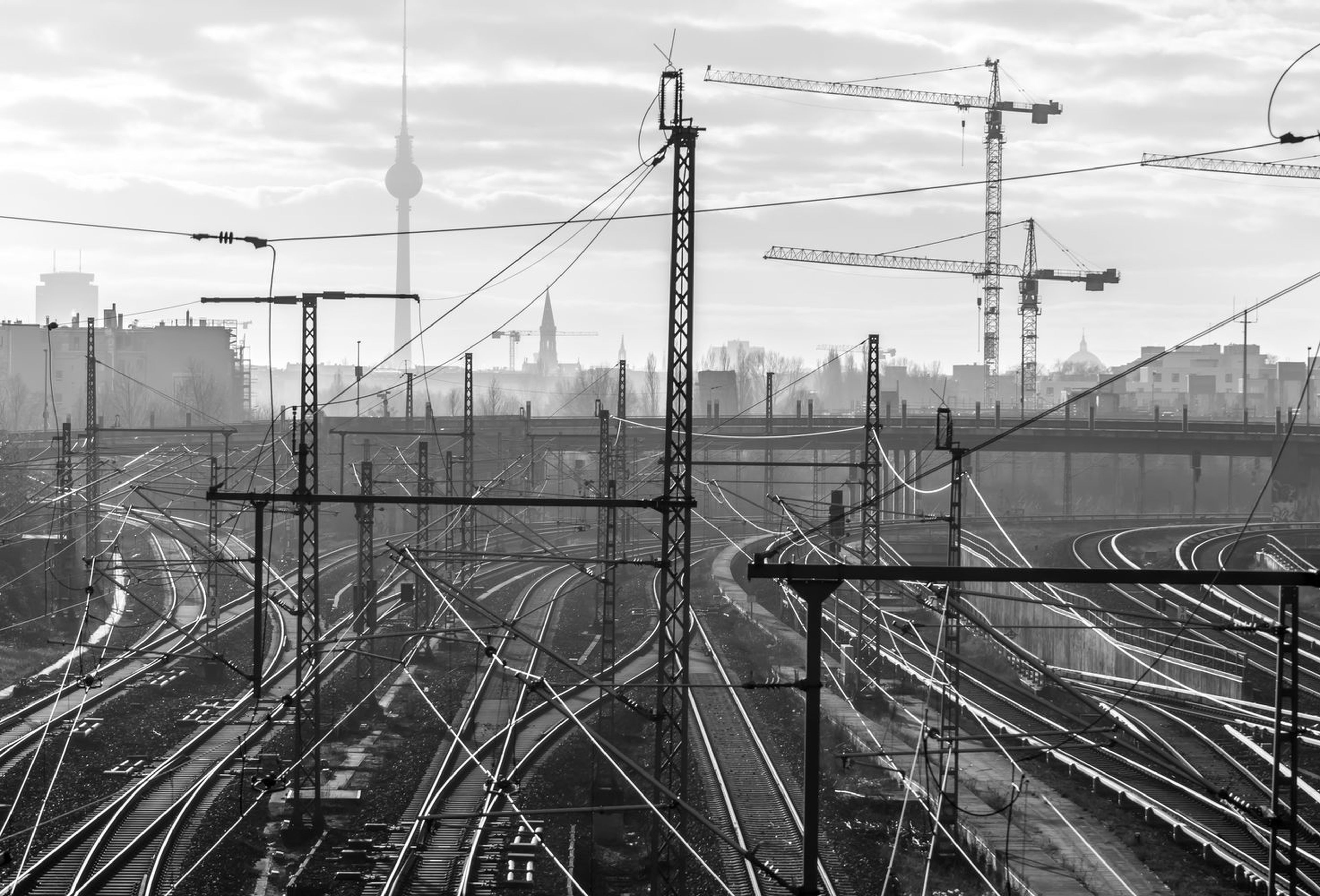 cable, electricity, power line, electricity pylon, sky, power supply, transportation, connection, fuel and power generation, outdoors, no people, building exterior, technology, cloud - sky, bridge - man made structure, city, built structure, day, business finance and industry, smoke - physical structure, suspension bridge, cityscape, architecture