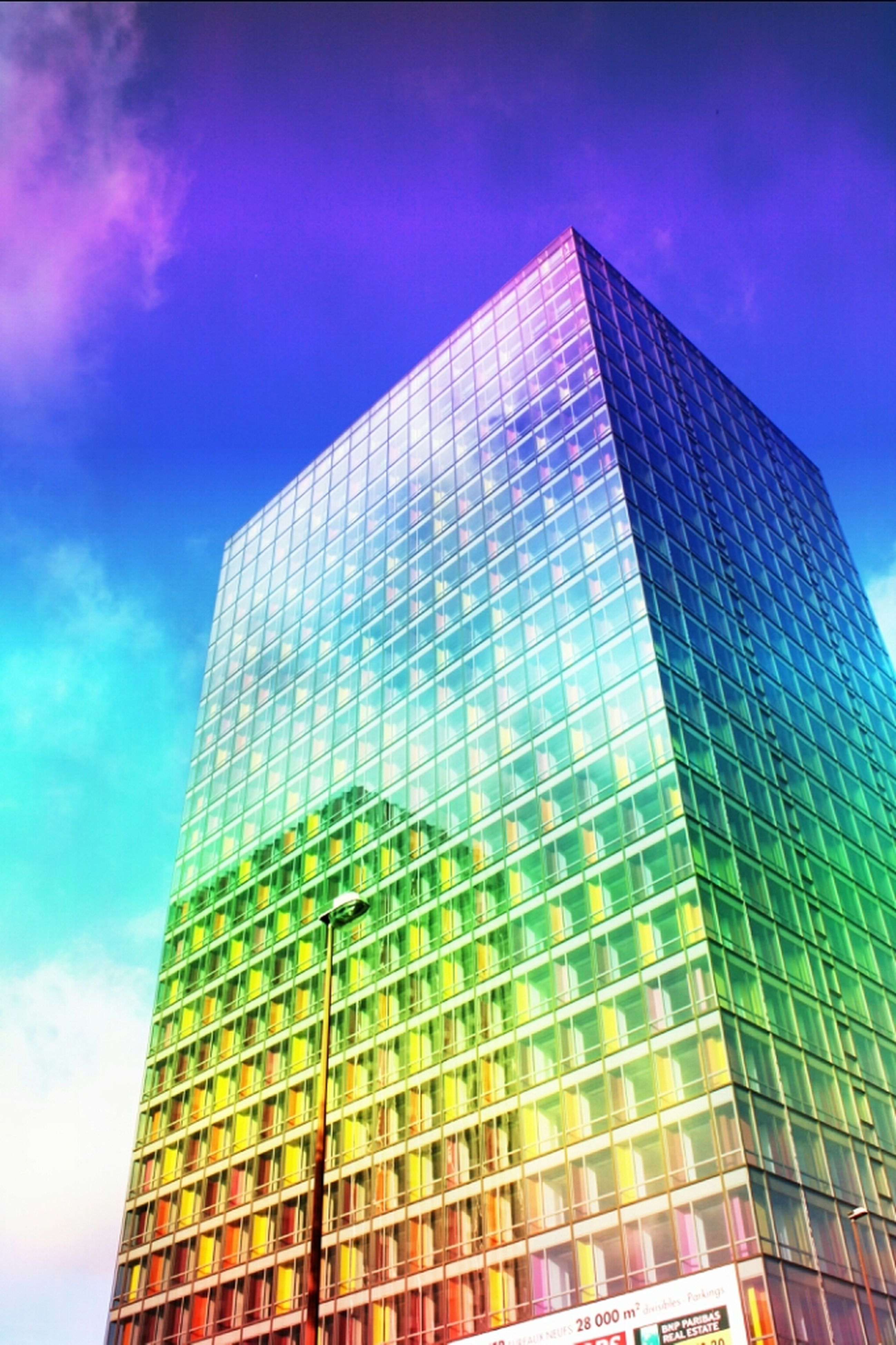 low angle view, architecture, building exterior, modern, built structure, office building, skyscraper, tall - high, city, tower, glass - material, sky, reflection, building, tall, cloud - sky, day, outdoors, no people, cloud