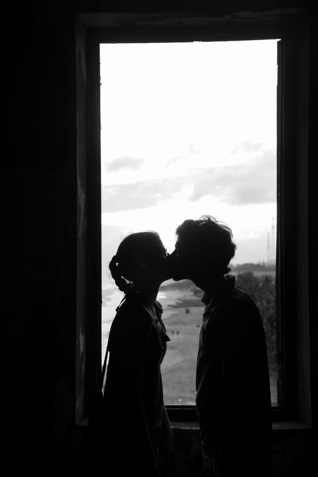 Black And White Blackandwhite Bonding Cloud Colors And Patterns Couple Dark Day In Front Of Indoors  Kiss Leisure Activity Lifestyles Love Men Outline Person Rear View Silhouette Sky Solitude Standing Togetherness Traveling Window
