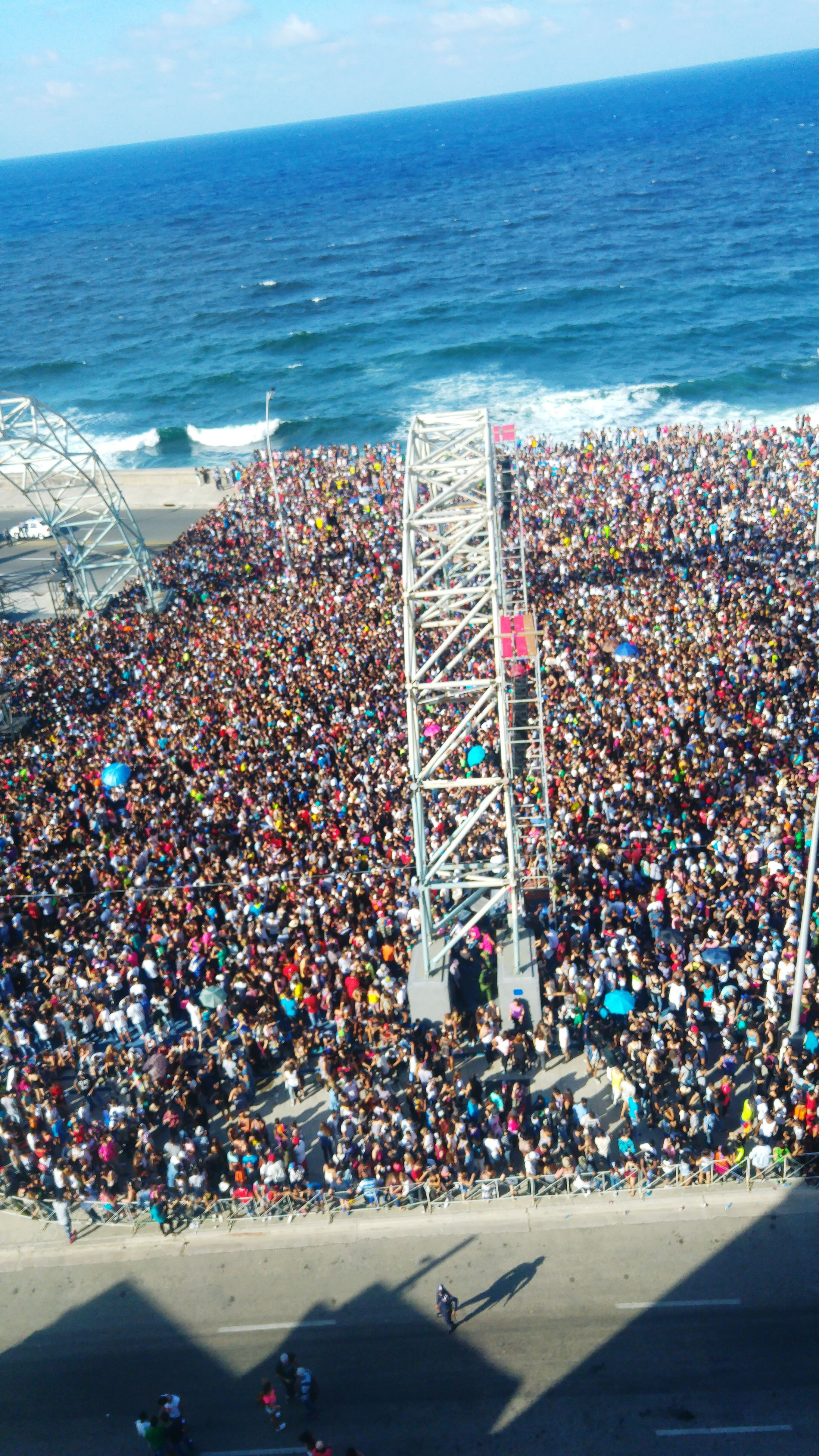 sea, water, horizon over water, large group of people, high angle view, beach, blue, crowded, shore, vacations, cityscape, city, built structure, tourism, outdoors, travel destinations, mixed age range, nature, travel