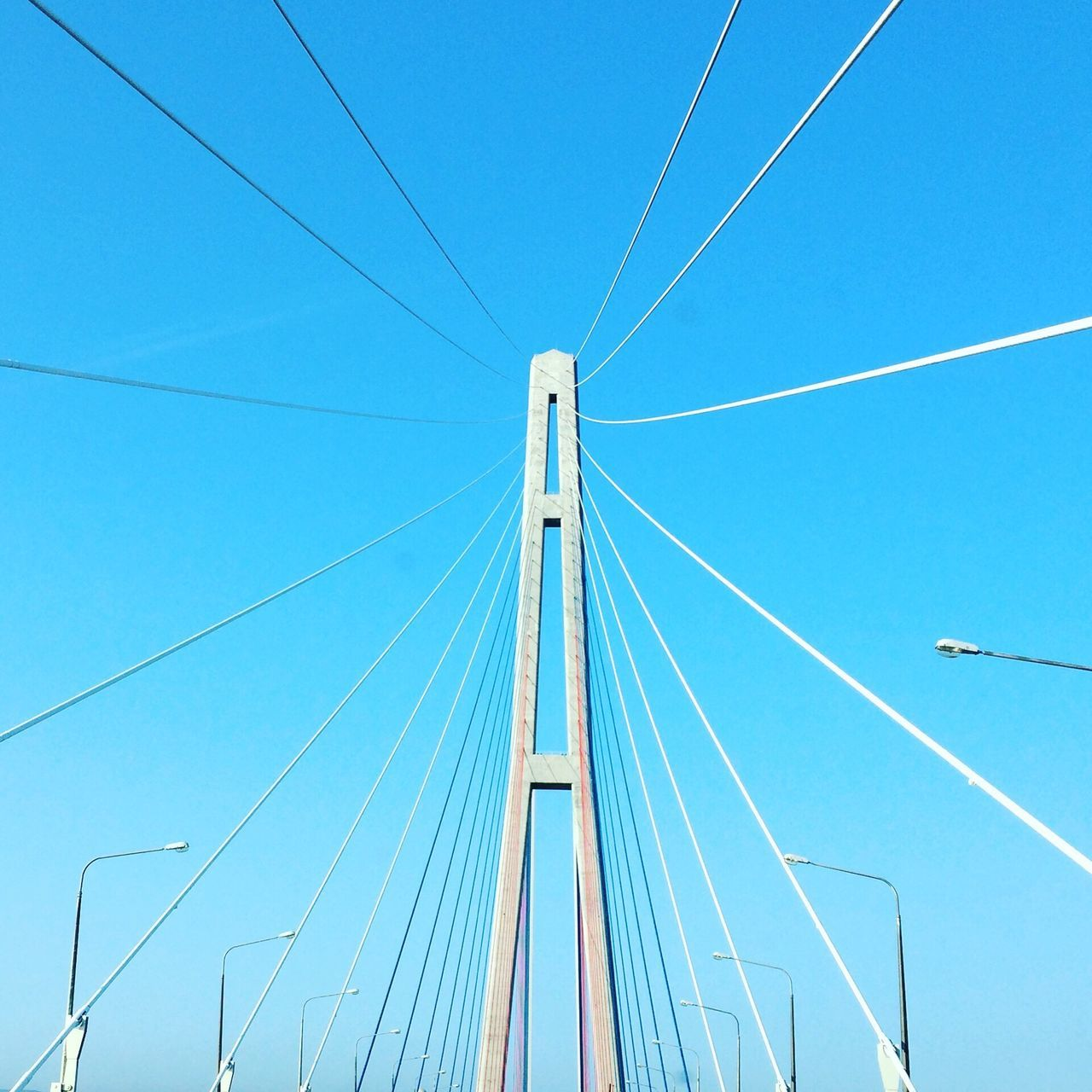cable, connection, blue, day, transportation, power line, low angle view, outdoors, clear sky, no people, suspension bridge, bridge - man made structure, built structure, parallel, line, sky, architecture