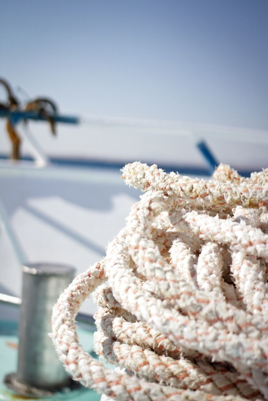 rope, no people, outdoors, close-up, day, focus on foreground, sea, sunlight, tied up, water, sky, nature