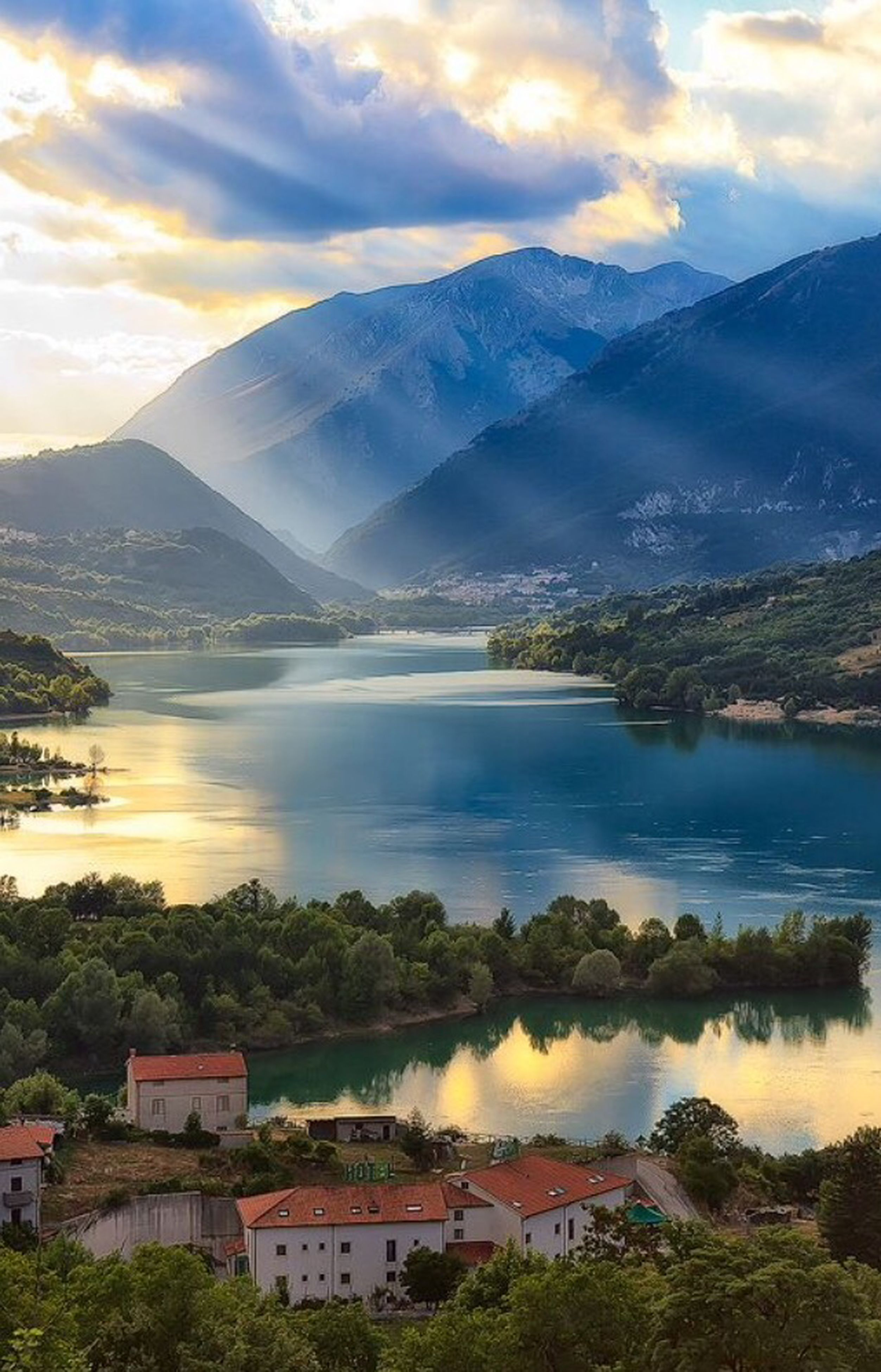mountain, mountain range, water, scenics, sky, tranquil scene, lake, beauty in nature, tranquility, tree, sunset, nature, cloud - sky, river, built structure, idyllic, landscape, building exterior, architecture, reflection