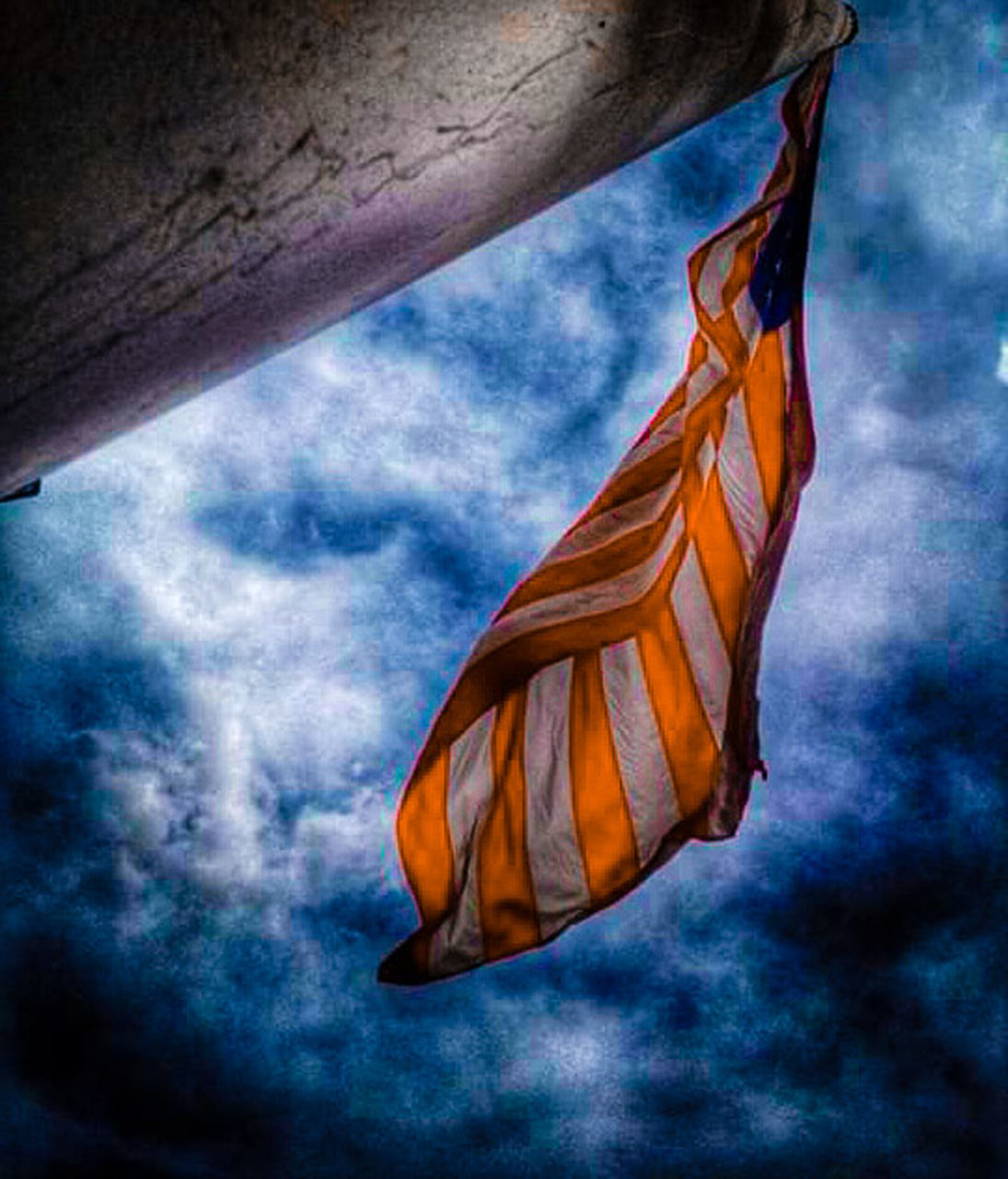 cloud - sky, low angle view, wind, flag, textile, no people, sky, day, blue, outdoors