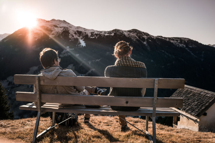 Friends enjoy mountain view Autumn Bench Friends Life Mountain View Nature Quality Time Story Telling Alps Friendship Live Authentic Mood Mountain Outdoors Real People Sunset