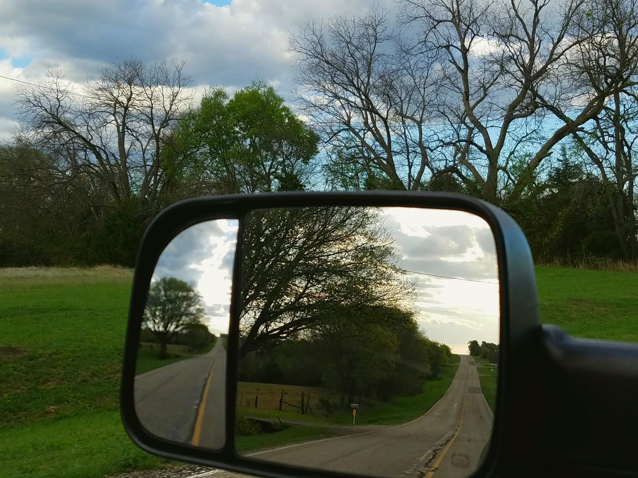 tree, side-view mirror, reflection, sky, grass, car, bare tree, nature, day, outdoors, transportation, land vehicle, road, landscape, vehicle mirror, no people, branch, beauty in nature