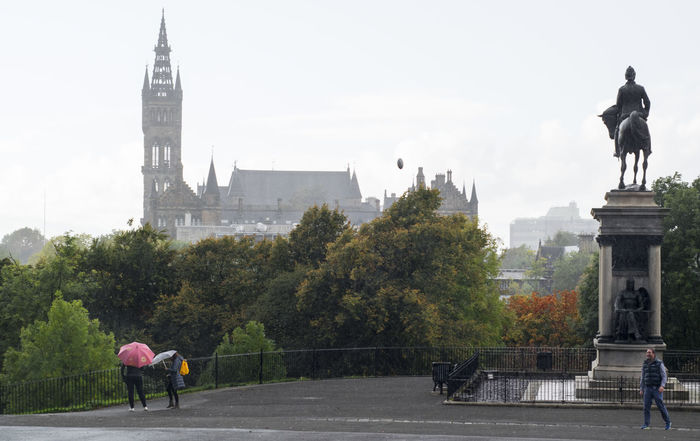 Glasgow  Glasgow University Kelvingrove Park Architecture Building Exterior Built Structure City Day History Leisure Activity Lifestyles Men Outdoors People Playing In The Rain Real People Sculpture Sky Statue Tourism Travel Destinations Tree Umbrella Women