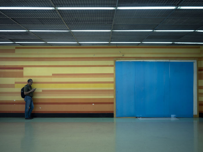 Architecture Built Structure Corrugated Iron Day Full Length Illuminated Indoors  One Person People Real People Yellow