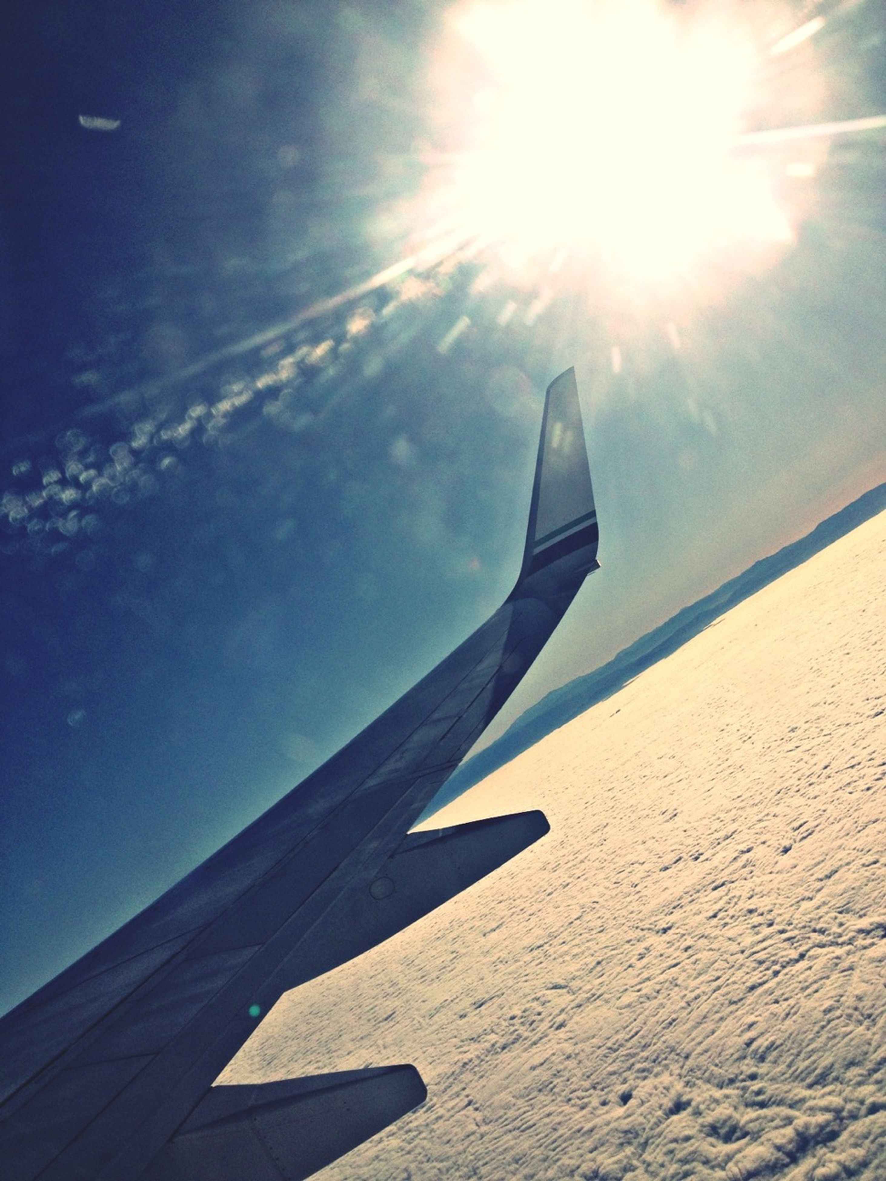 sun, sunlight, transportation, aircraft wing, sunbeam, airplane, flying, sky, lens flare, sunny, mode of transport, air vehicle, part of, low angle view, cropped, blue, travel, mid-air, journey, day