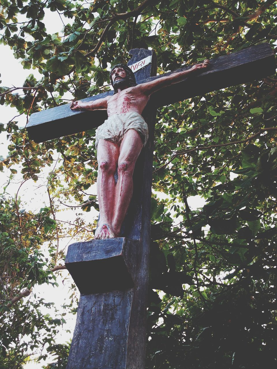 tree, human representation, sculpture, male likeness, statue, low angle view, art and craft, day, crucifix, cross, religion, no people, spirituality, scarecrow, hanging, outdoors, sky, close-up
