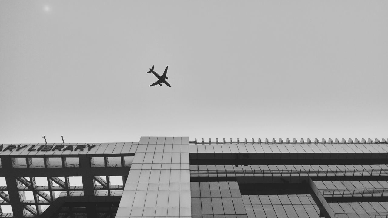 flying, low angle view, airplane, clear sky, transportation, journey, mid-air, architecture, outdoors, air vehicle, no people, day, building exterior, sky