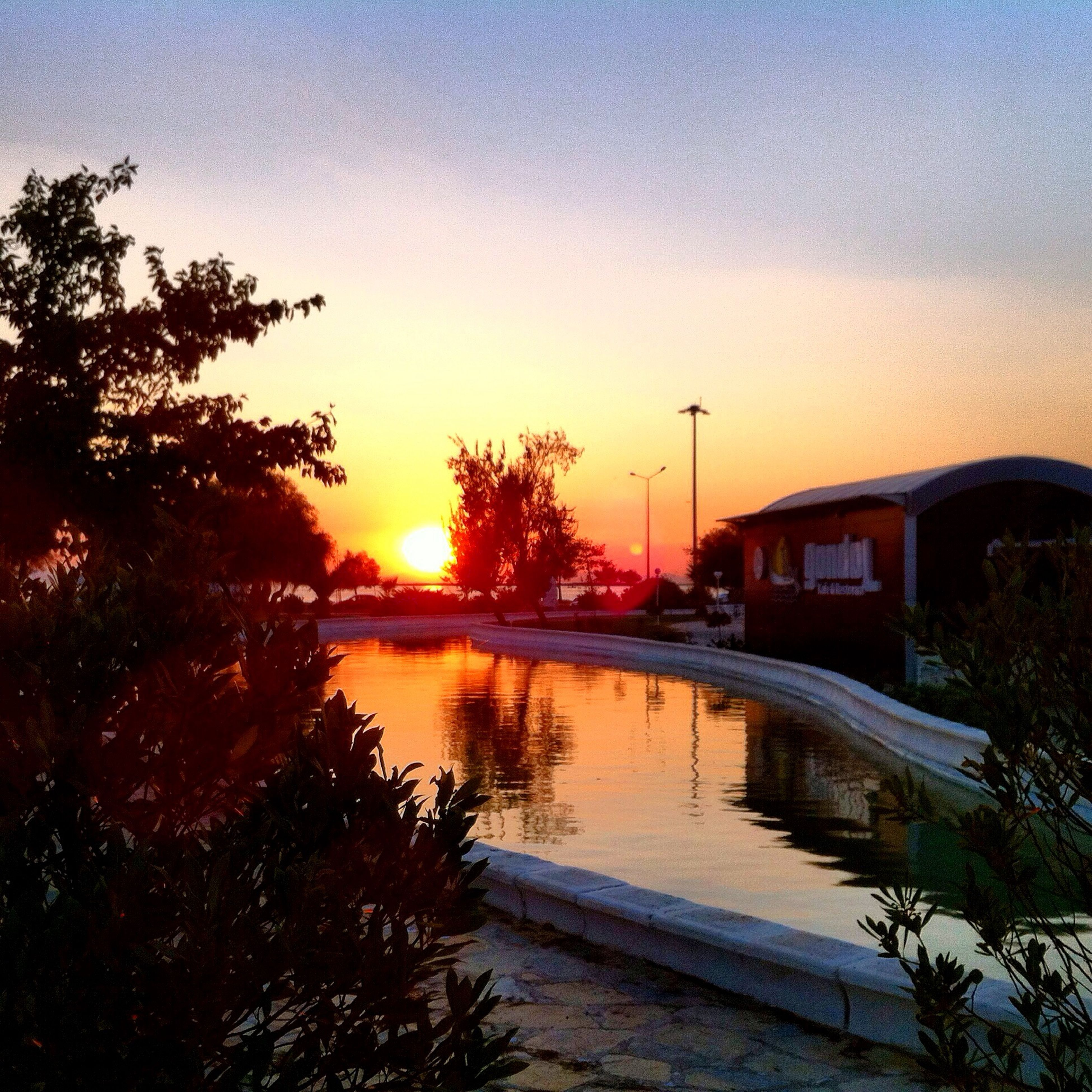 sunset, water, reflection, tree, orange color, sky, built structure, canal, transportation, river, tranquility, architecture, nature, beauty in nature, lake, clear sky, tranquil scene, building exterior, scenics, mode of transport