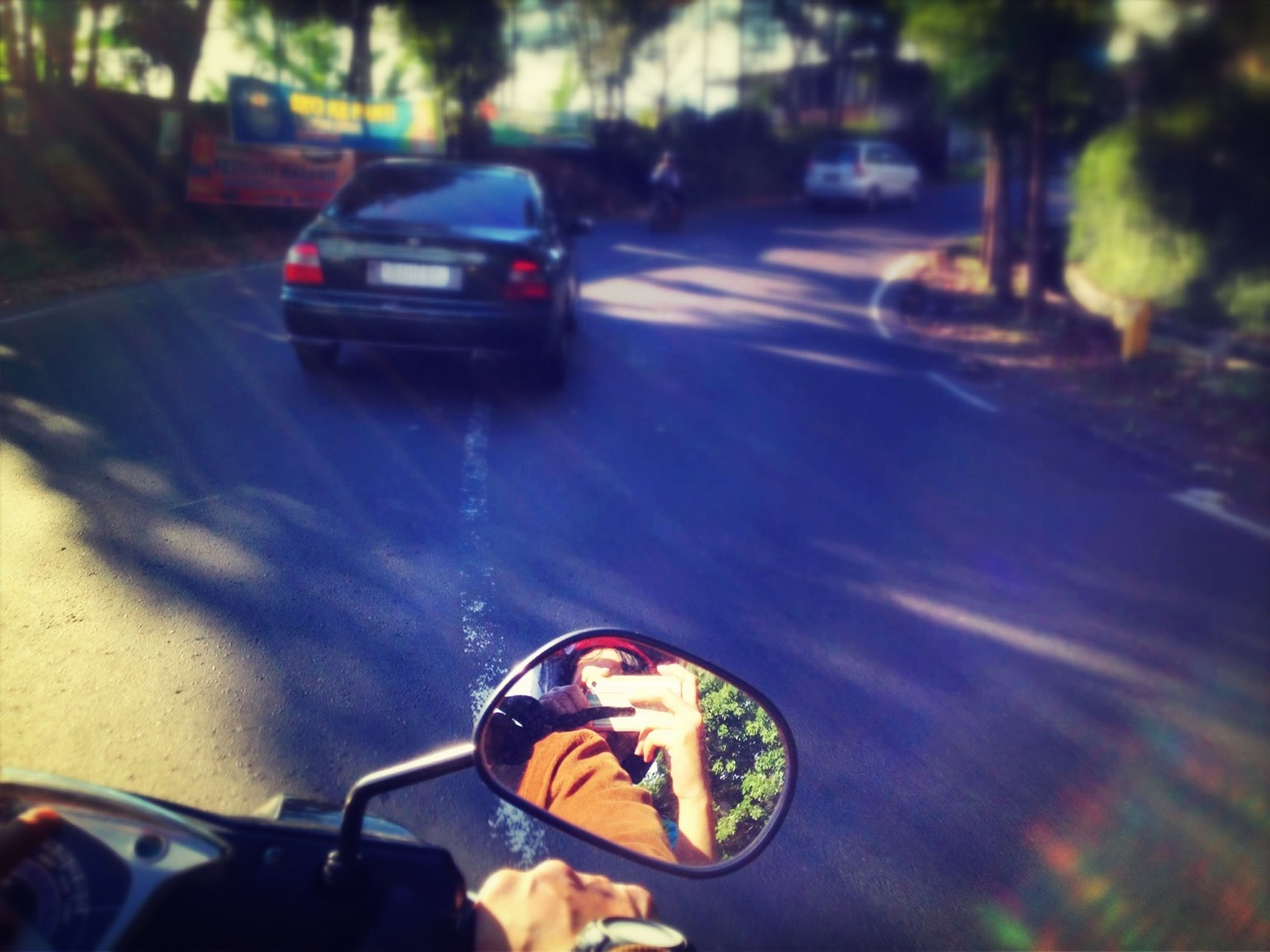 transportation, mode of transport, land vehicle, car, street, stationary, bicycle, travel, road, parking, on the move, parked, reflection, motorcycle, side-view mirror, part of, outdoors, sunlight, headlight, tree