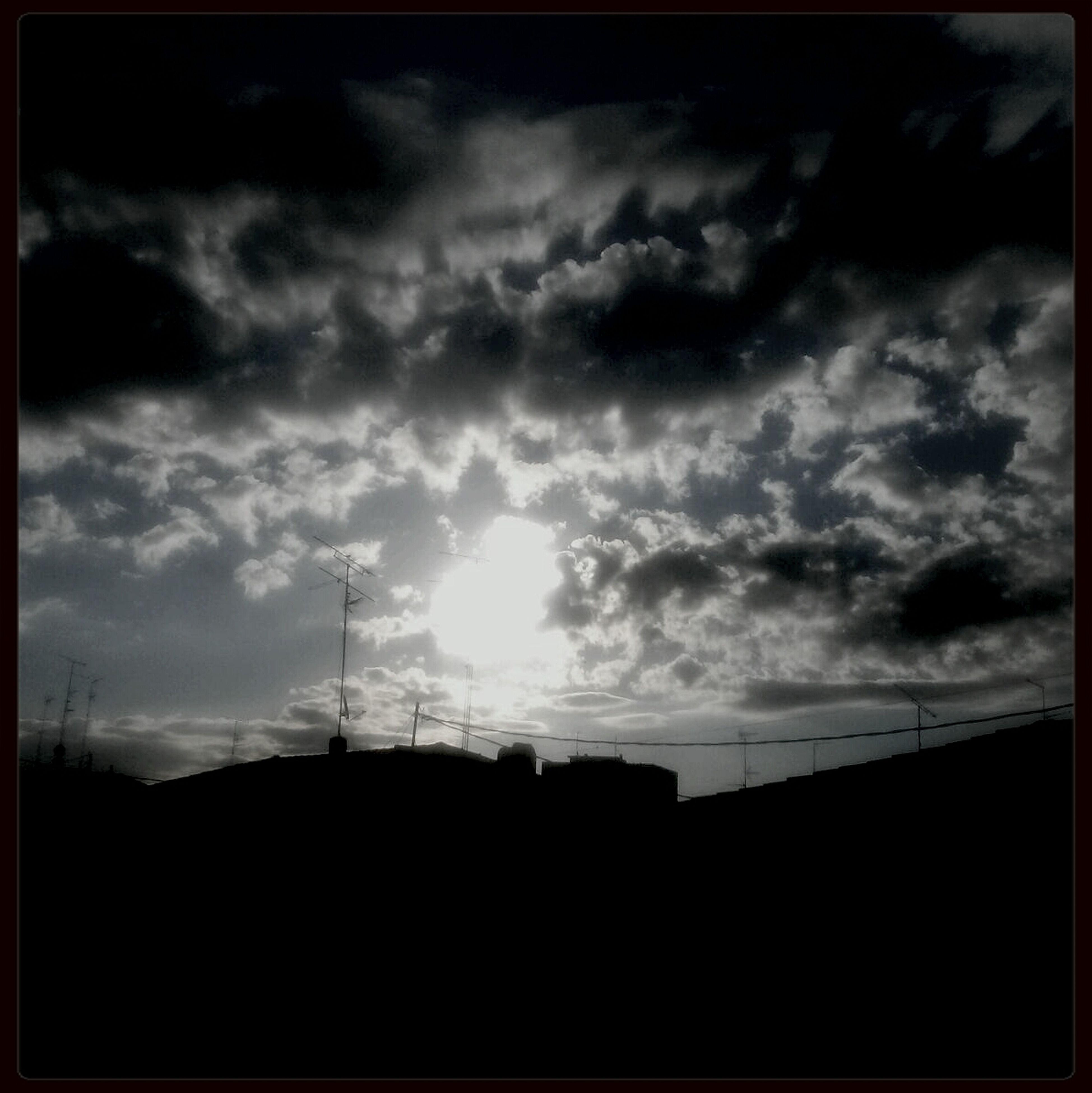 silhouette, sky, cloud - sky, low angle view, built structure, building exterior, architecture, cloudy, sunset, cloud, electricity pylon, power line, weather, overcast, transfer print, dusk, nature, dark, outdoors, house