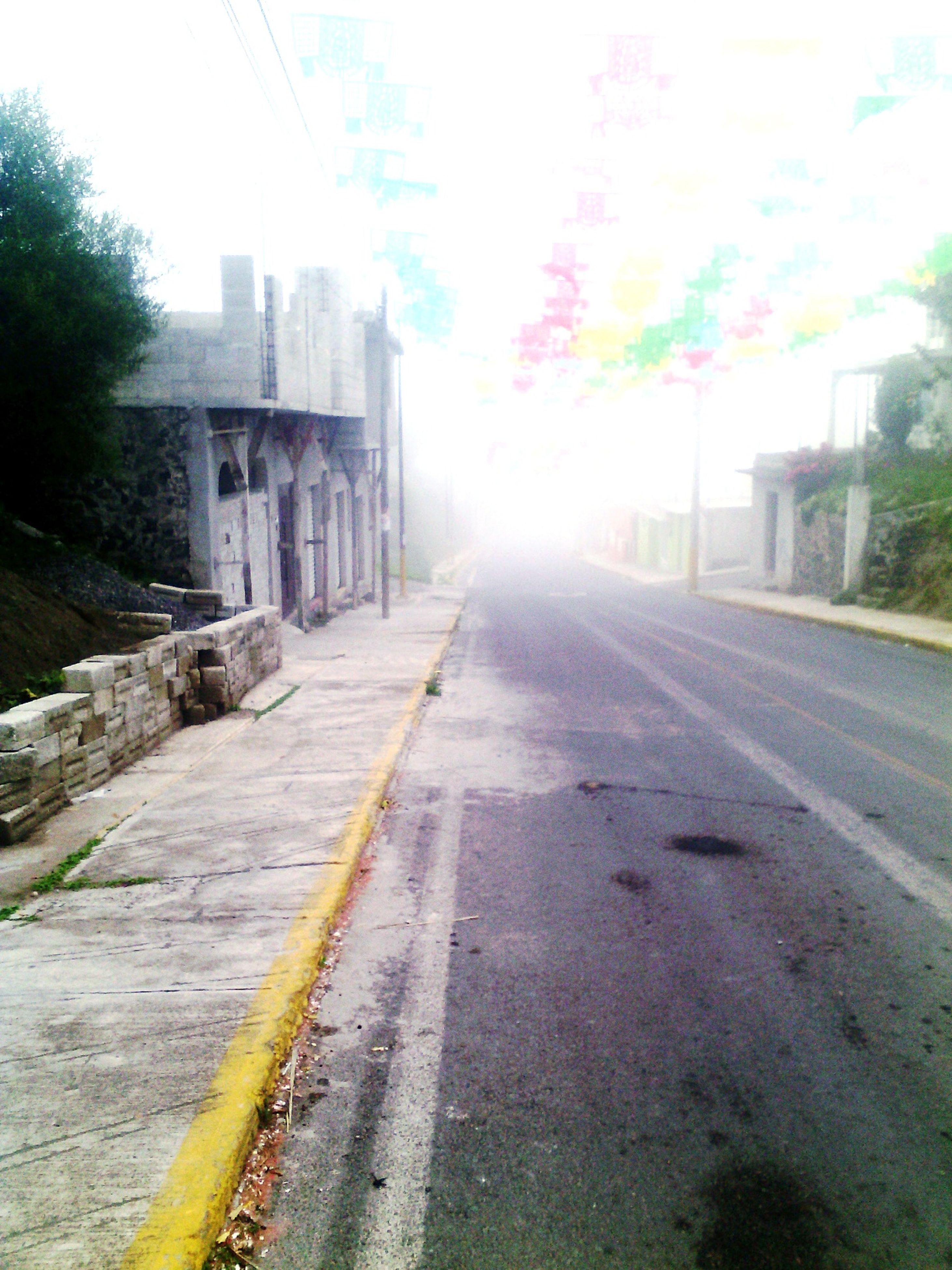 architecture, building exterior, built structure, city, street, road, transportation, road marking, the way forward, empty, long, outdoors, surface level, day, empty road, diminishing perspective, sky, narrow, lens flare, city life, no people, mist