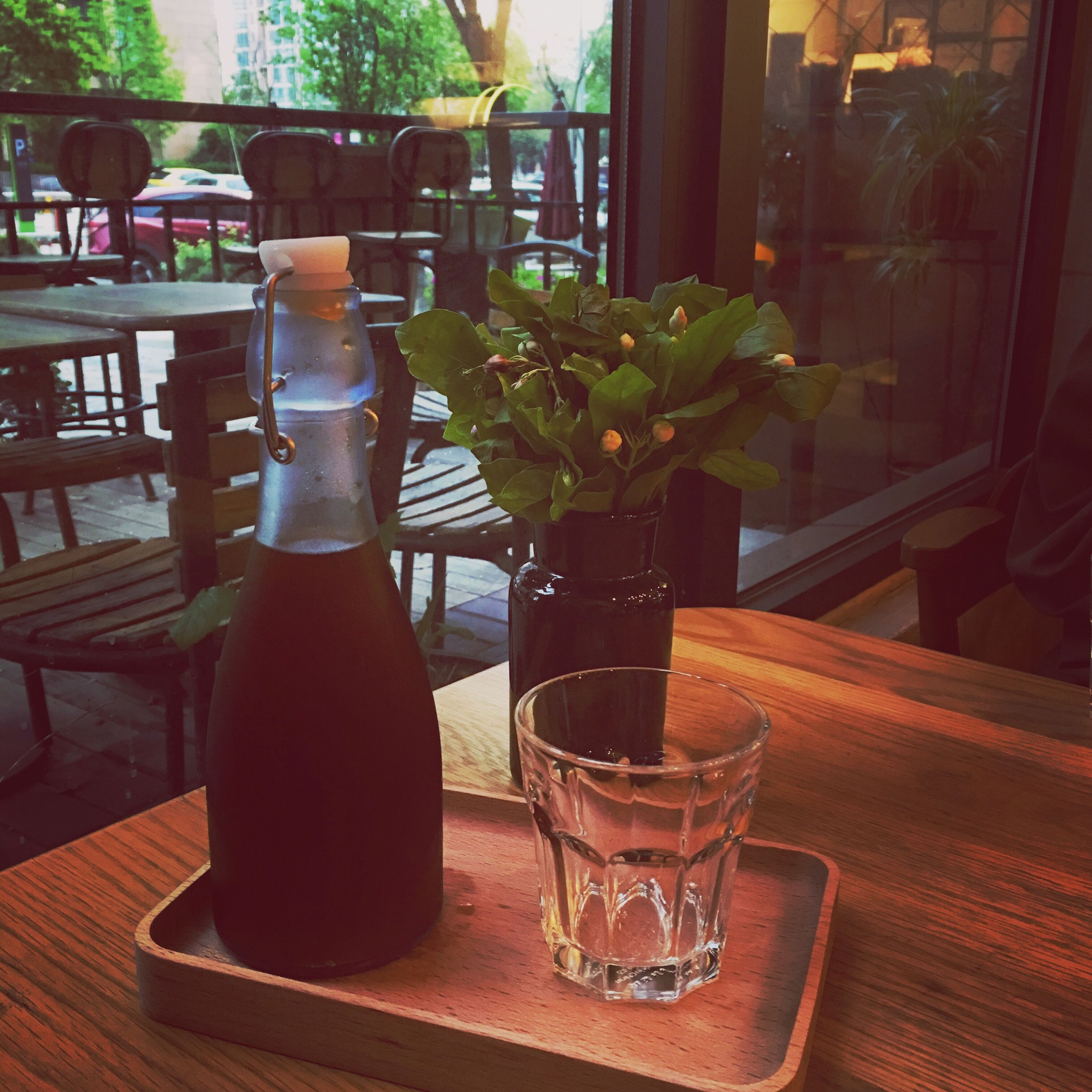table, indoors, drink, food and drink, freshness, drinking glass, glass - material, chair, potted plant, restaurant, vase, refreshment, still life, wood - material, glass, window, transparent, home interior, sunlight, close-up