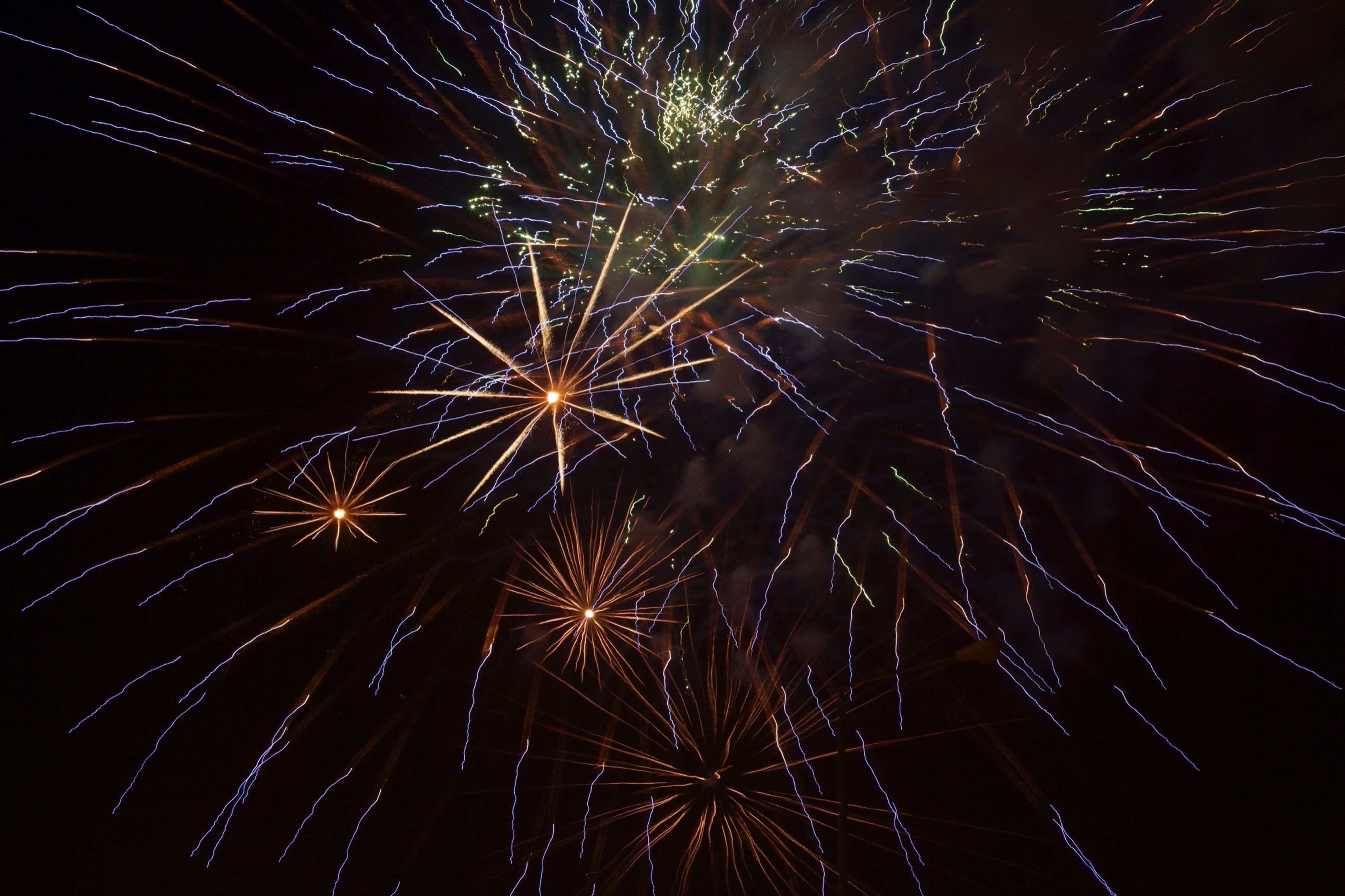 firework display, night, celebration, exploding, low angle view, long exposure, motion, firework - man made object, glowing, illuminated, sparks, arts culture and entertainment, firework, event, sky, entertainment, blurred motion, celebration event, outdoors, no people