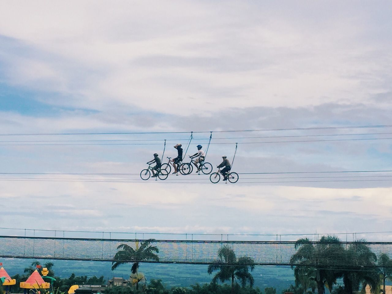 Low Angle View Of People Zip Line Cycling Against Sky