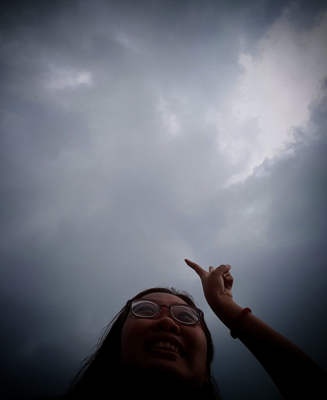 sky, one person, low angle view, cloud - sky, real people, gesturing, outdoors, day, headshot, human body part, young women, human hand, nature, young adult, close-up, people