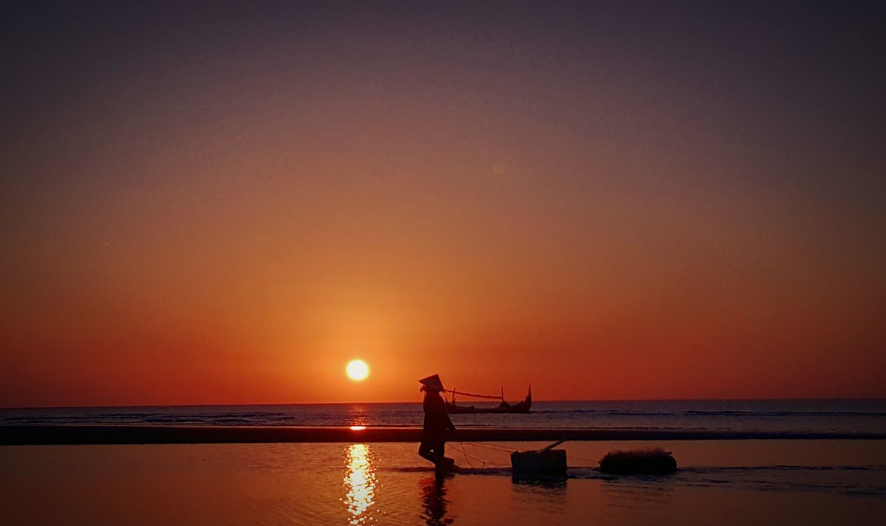 Silhouette Fisherman Standing On Shore Against During Sunset