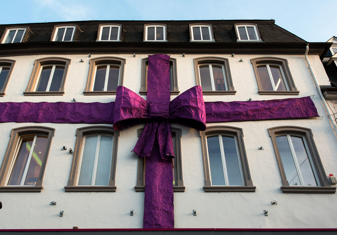 Violet huge ribbon on a building facade. Christmas time. BIG Bow Building Exterior Celebration Christmas Day December Decor Decorated Decoration Event Facade Building Germany Holiday Huge New Year Outdoors Purple Ribbon Seasonal Symbol Trier, Germany's Oldest City Violet Wall - Building Feature Windows