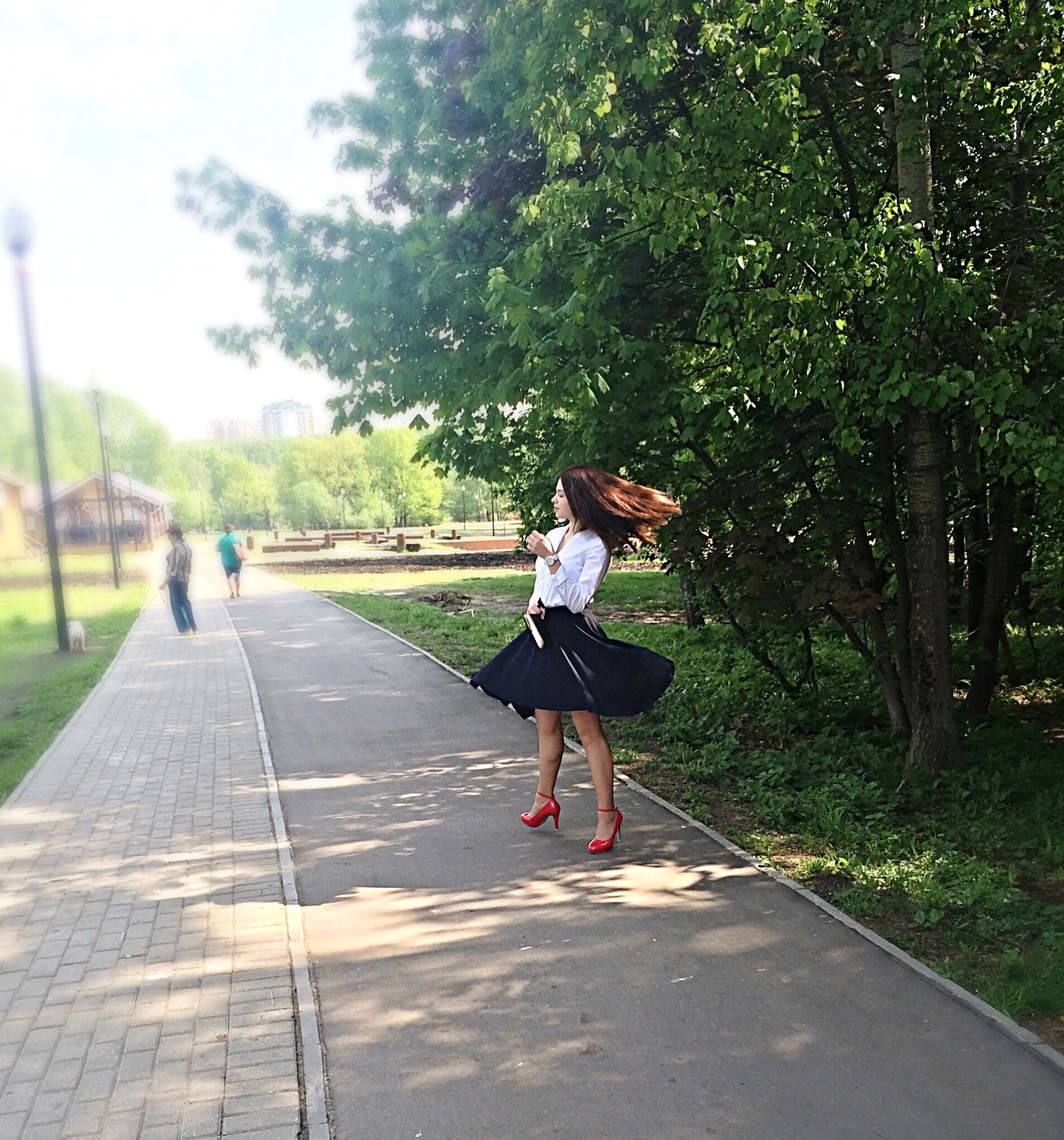 full length, tree, lifestyles, leisure activity, road, the way forward, casual clothing, transportation, mid-air, rear view, walking, street, front view, skateboard, day, jumping, young adult, motion