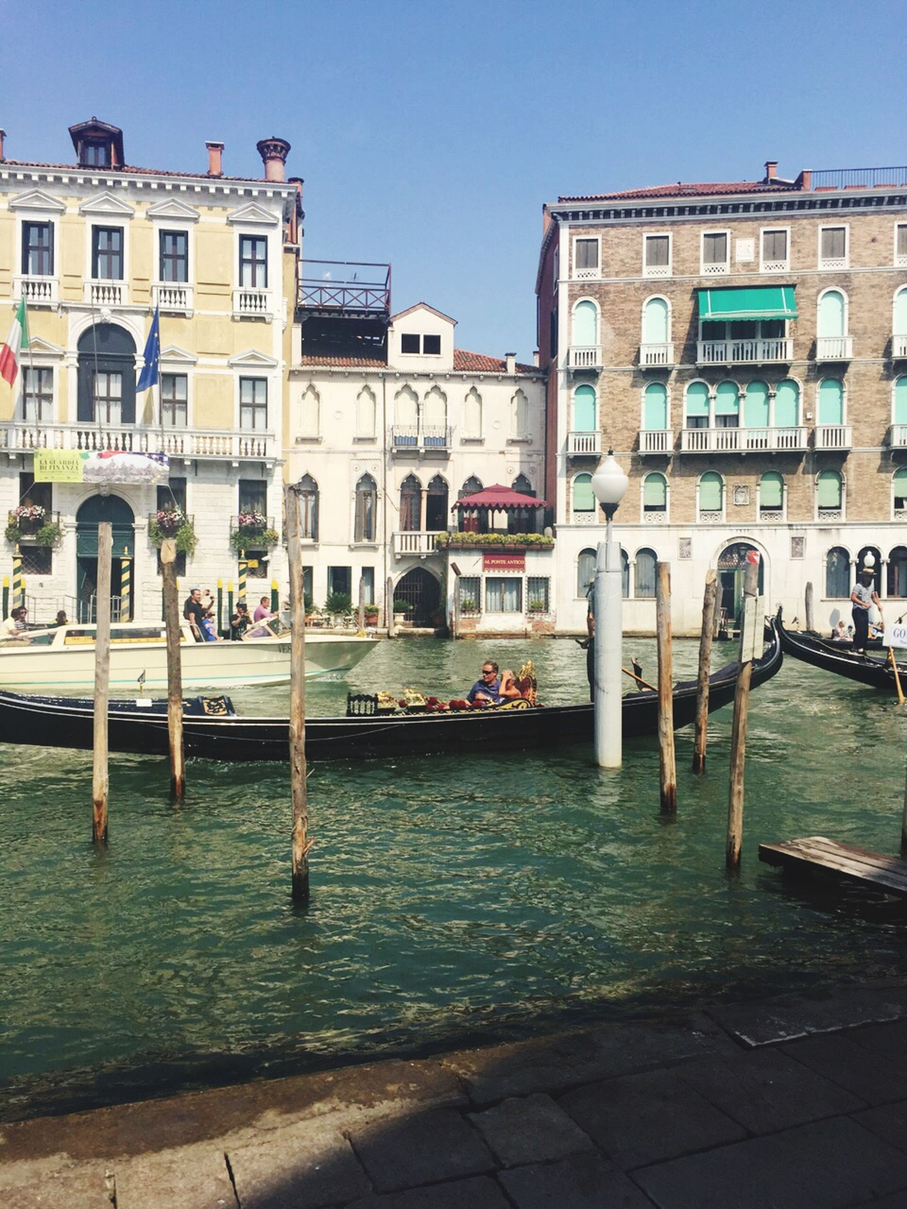architecture, building exterior, built structure, water, clear sky, canal, city, incidental people, building, waterfront, reflection, residential building, day, sky, sunlight, outdoors, travel destinations, rippled, residential structure, city life