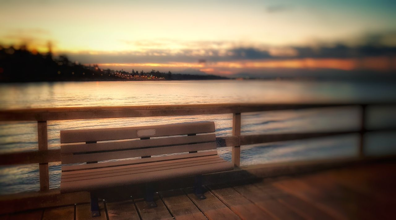Water Bench Selective Focus Tranquility Wooden Tranquil Scene Orange Color Sky Sea No People Beauty In Nature Ocean Scenics Waterfront Surface Level Blue Railings Footpath Walkway Clear Sky Weathered Creativity Historic Non-urban Scene Nature