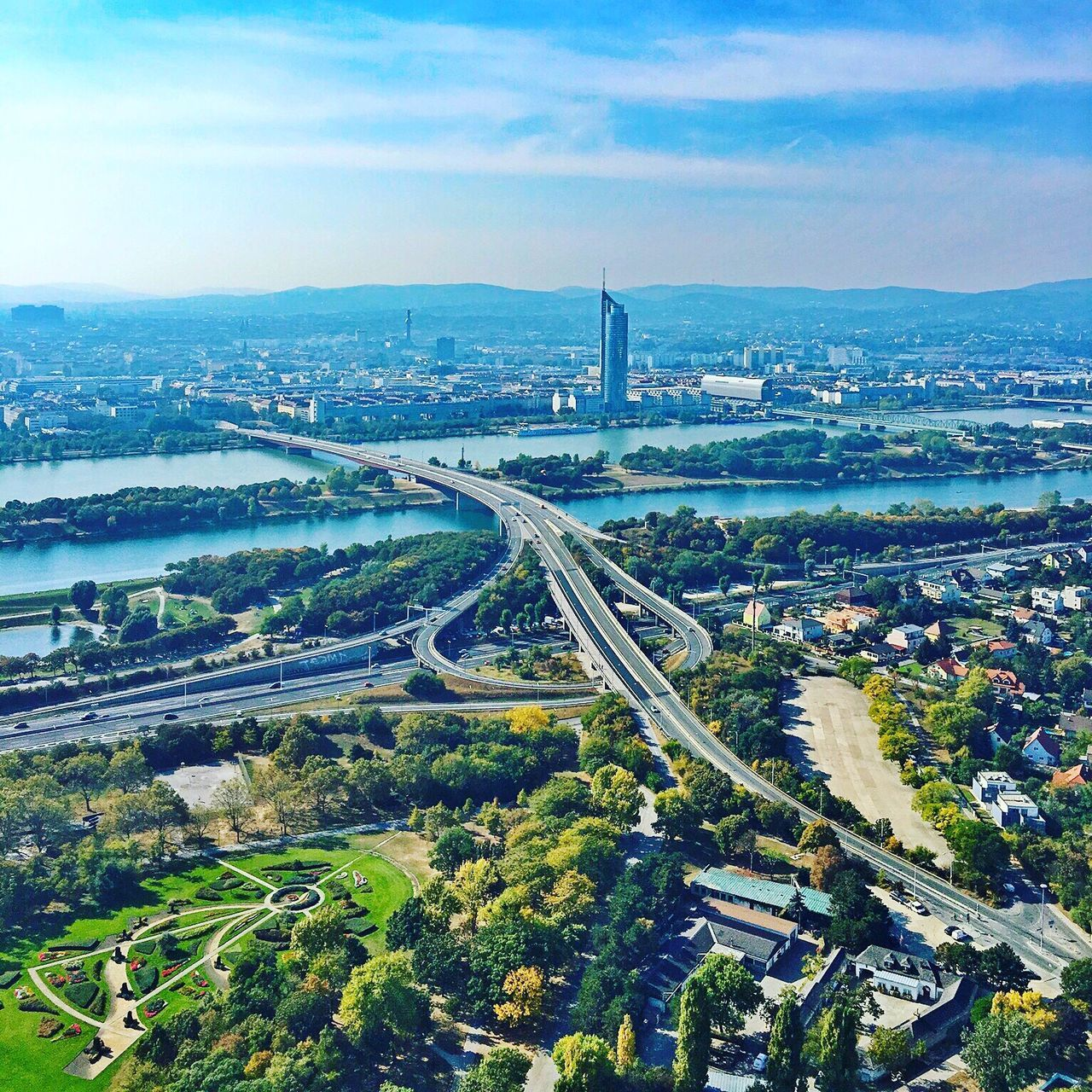 architecture, city, connection, built structure, aerial view, cityscape, transportation, road, high angle view, bridge - man made structure, sky, building exterior, no people, city life, outdoors, skyscraper, travel destinations, river, day, water