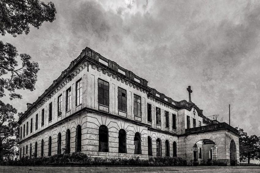 Low angle panorama of the old Diplomat Hotel on Dominican Hill in Baguio City, Philippines. I processed this in black and white and added a grunge overlay, which is actually a shot of a textured wall from inside the ruined building. Building Exterior Architecture Travel Destinations History Low Angle View Cloud - Sky No People Ruins Abandoned Abandoned Buildings Abandoned & Derelict Monochrome Black And White