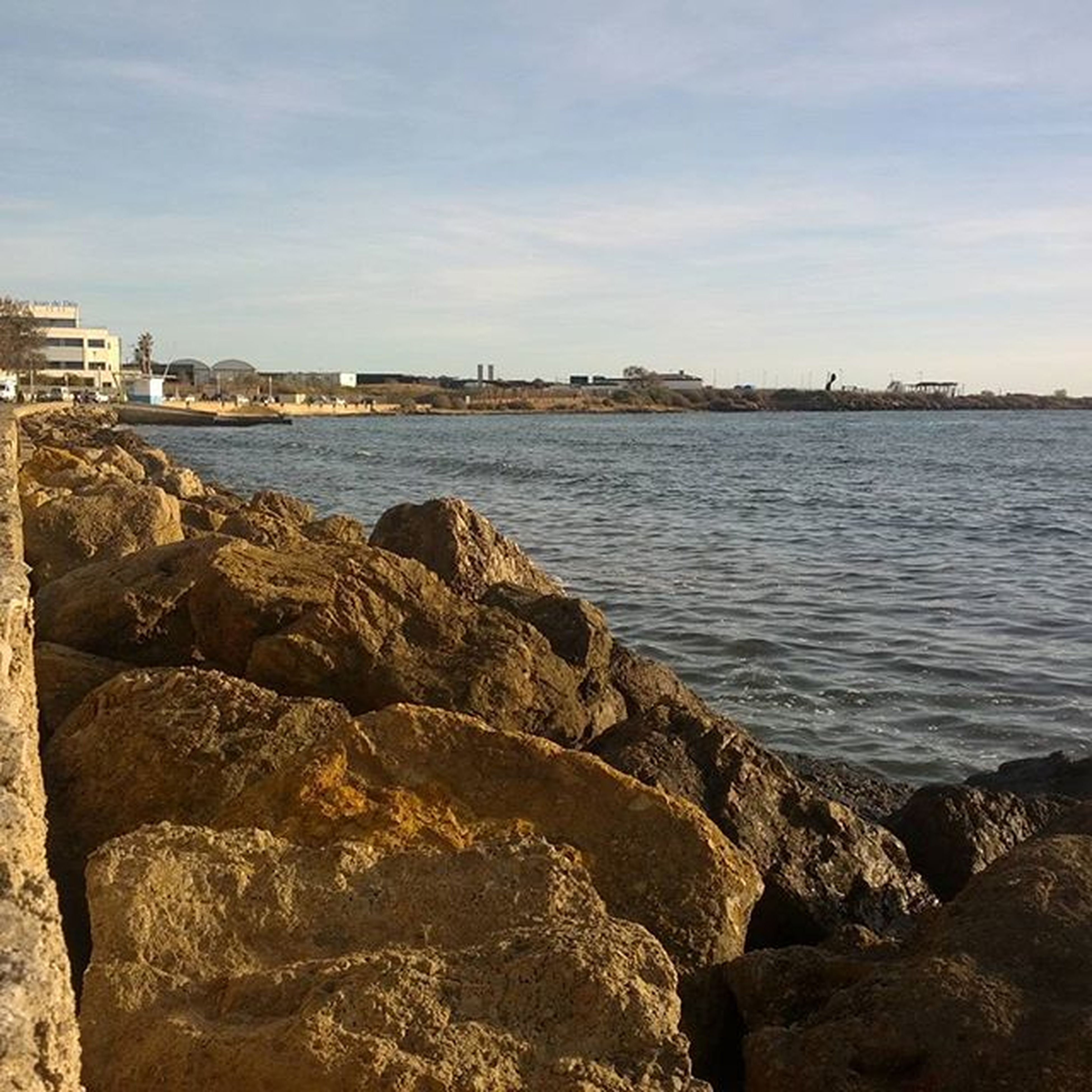 water, sea, architecture, building exterior, built structure, sky, city, cityscape, rock - object, river, cloud - sky, nature, coastline, day, scenics, shore, outdoors, cloud, no people, tranquility