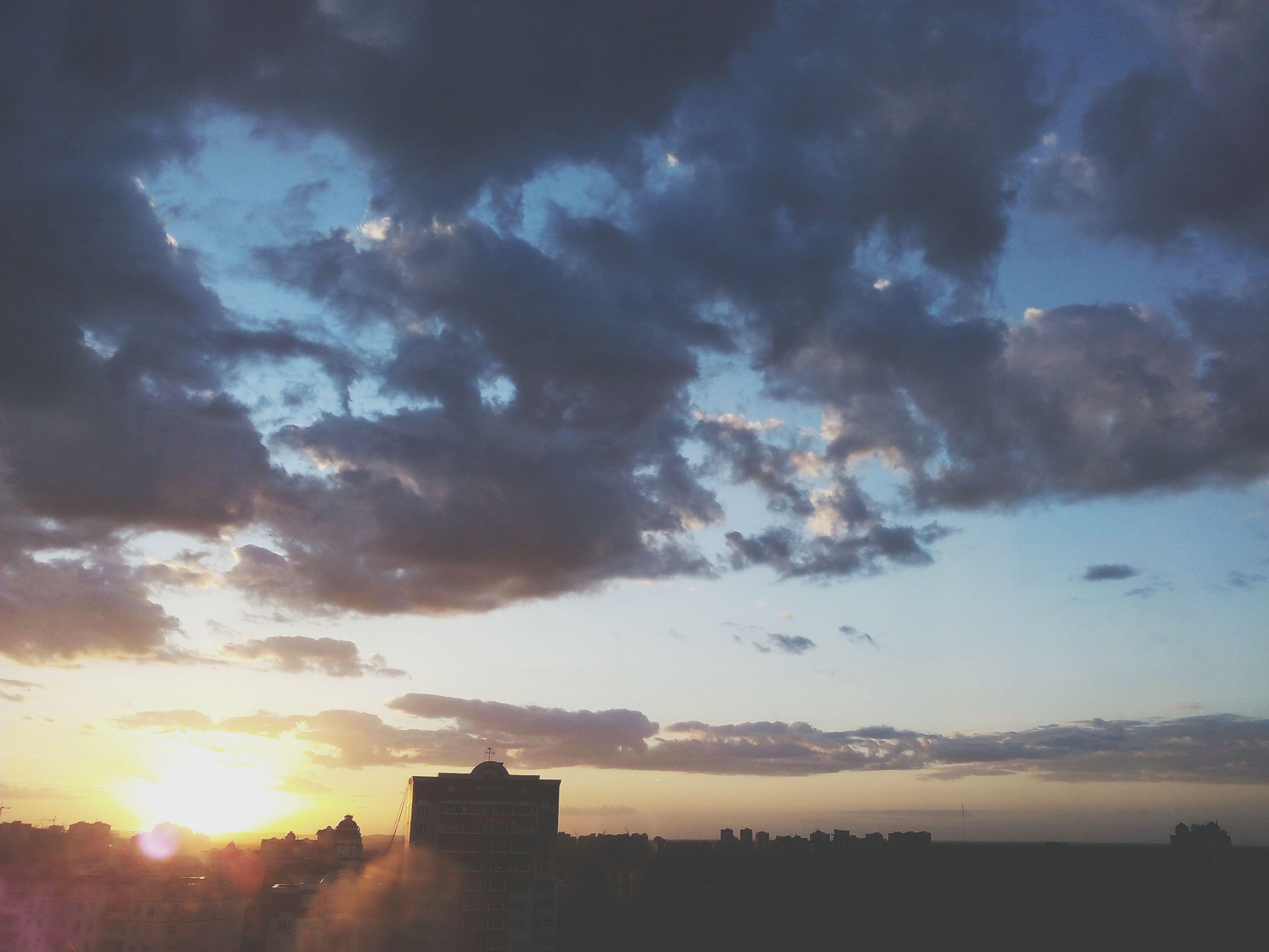 sunset, sky, building exterior, sun, architecture, cloud - sky, silhouette, built structure, sunbeam, sunlight, orange color, cloudy, cloud, city, nature, beauty in nature, building, weather, scenics, low angle view