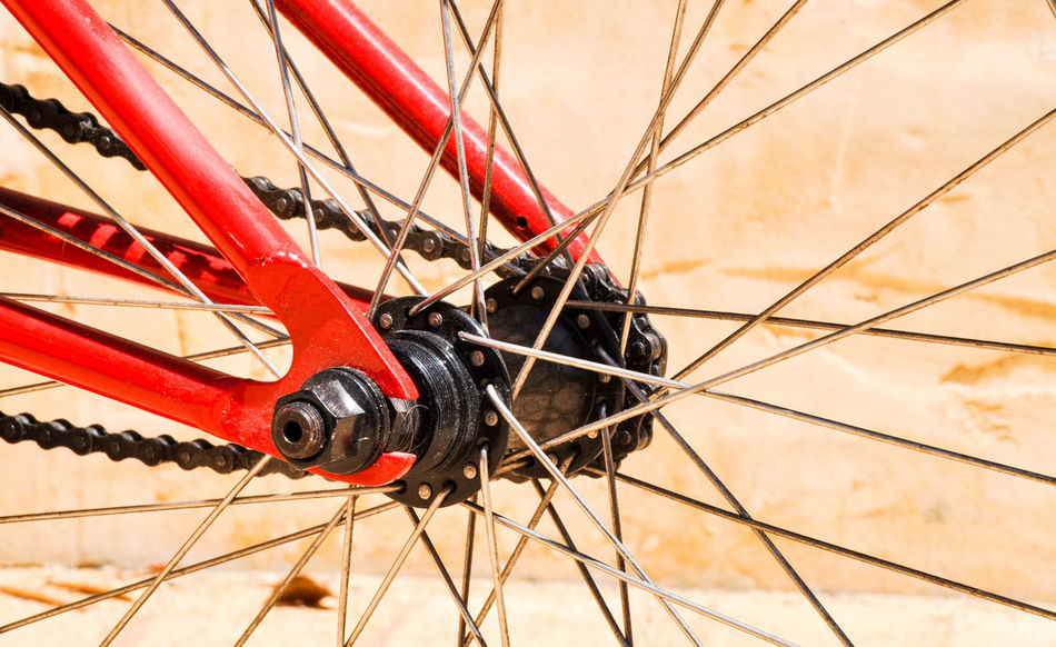 Abstract close-up of red bicycle with hub, spokes and chain. Abstract Bicycle Bike Bike Chain Chain Close-up Day Full Frame Hub Low Angle View Metal Outdoors Radiating Recreation  Red Spoke Spokes Sport Toy Transportation Wheel