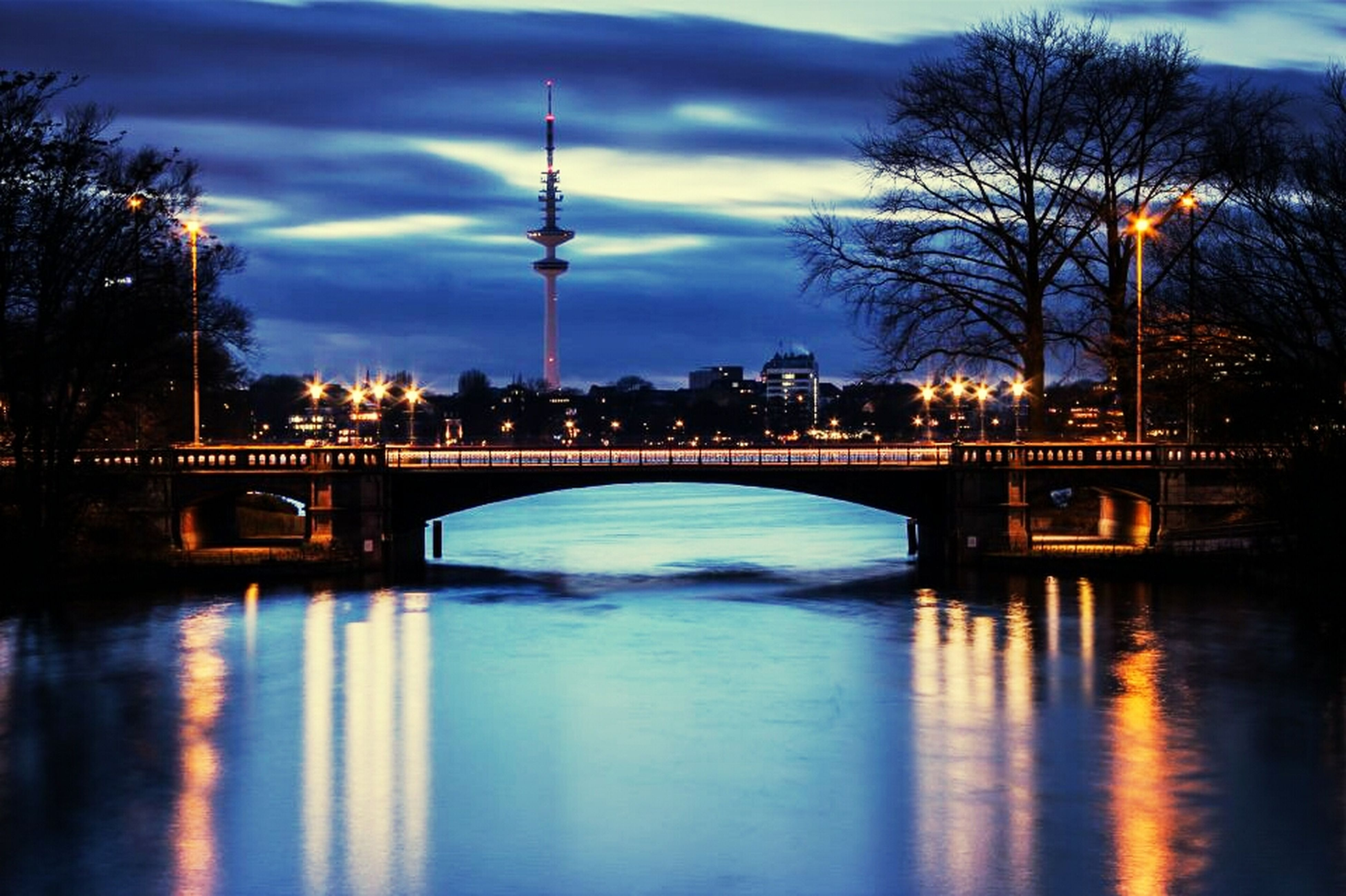 connection, water, built structure, architecture, bridge - man made structure, sky, waterfront, river, reflection, bridge, cloud - sky, tree, arch bridge, illuminated, sunset, dusk, cloud, engineering, tranquility, silhouette