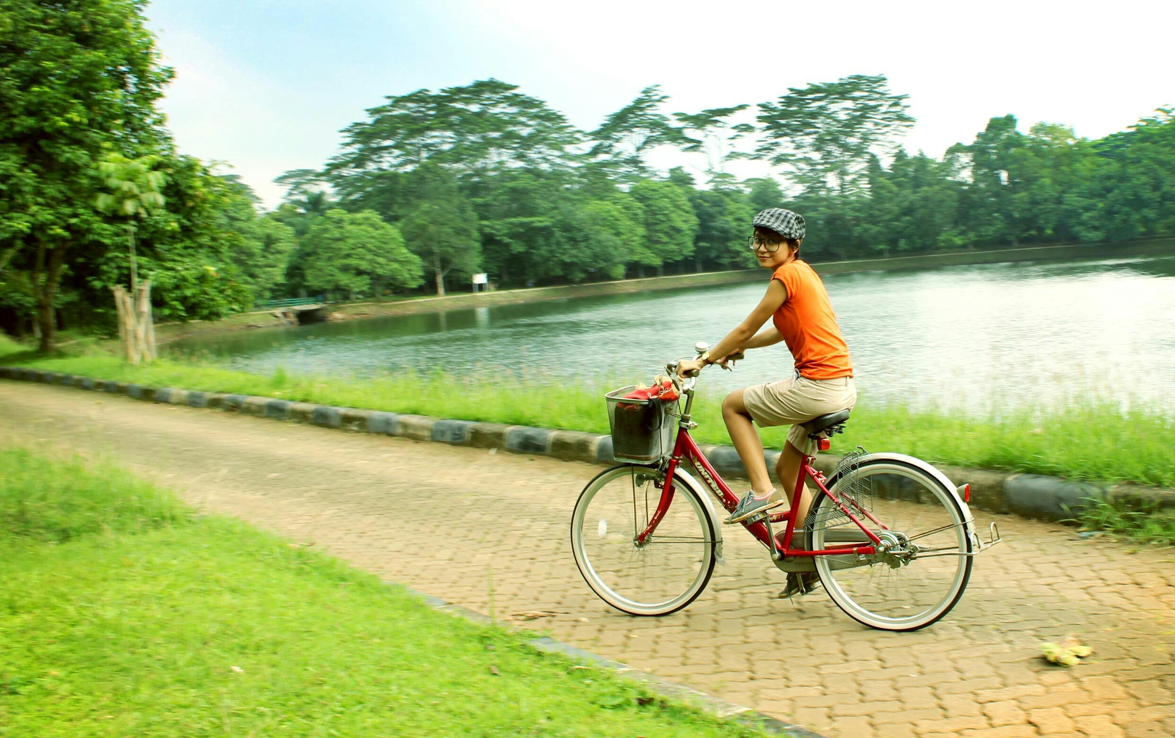 bicycle, transportation, mode of transport, riding, tree, lifestyles, leisure activity, full length, land vehicle, water, grass, travel, cycling, men, casual clothing, side view, river, sky