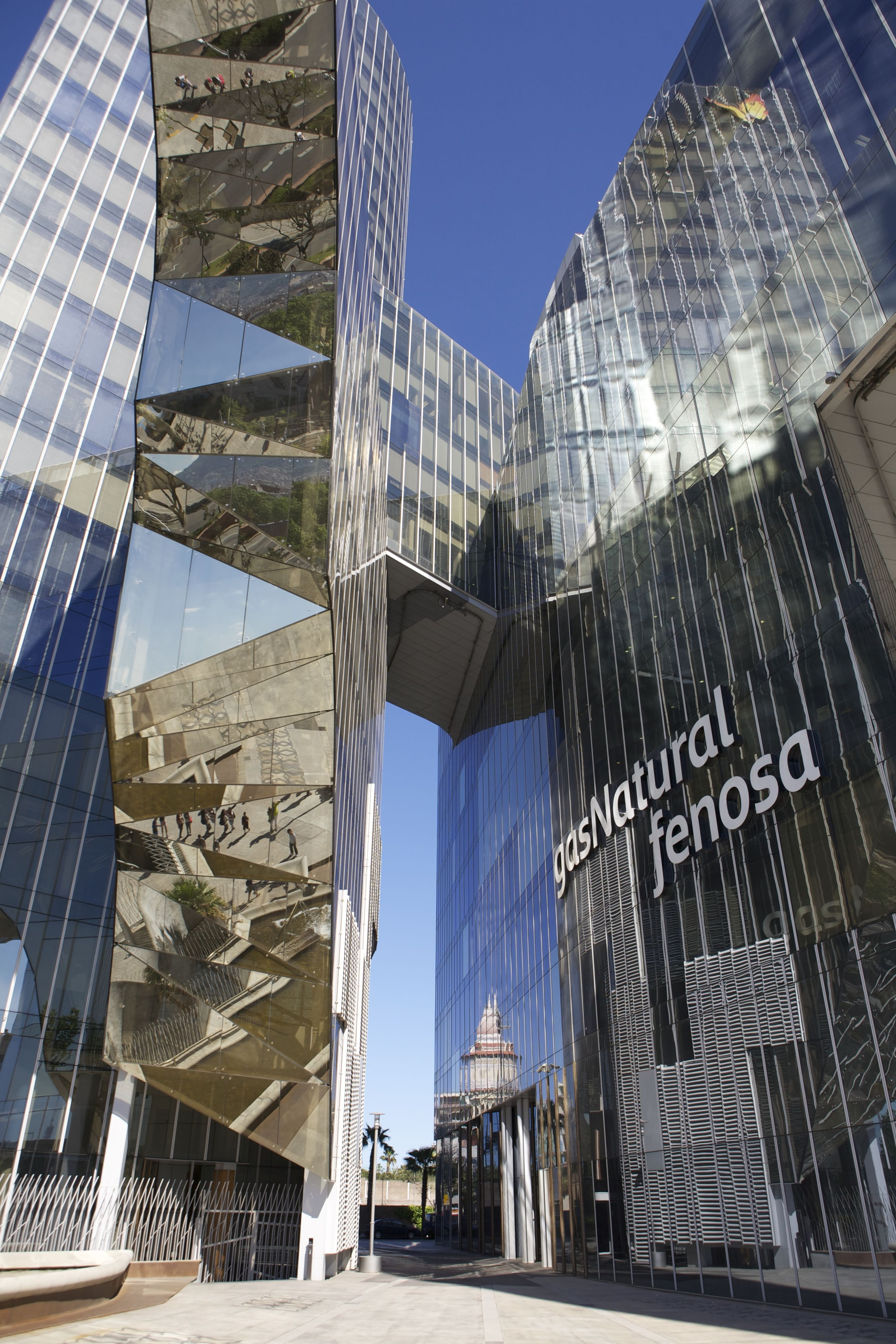 building exterior, architecture, built structure, city, modern, office building, skyscraper, building, tall - high, tower, low angle view, glass - material, reflection, blue, city life, residential building, sunlight, day, financial district, clear sky