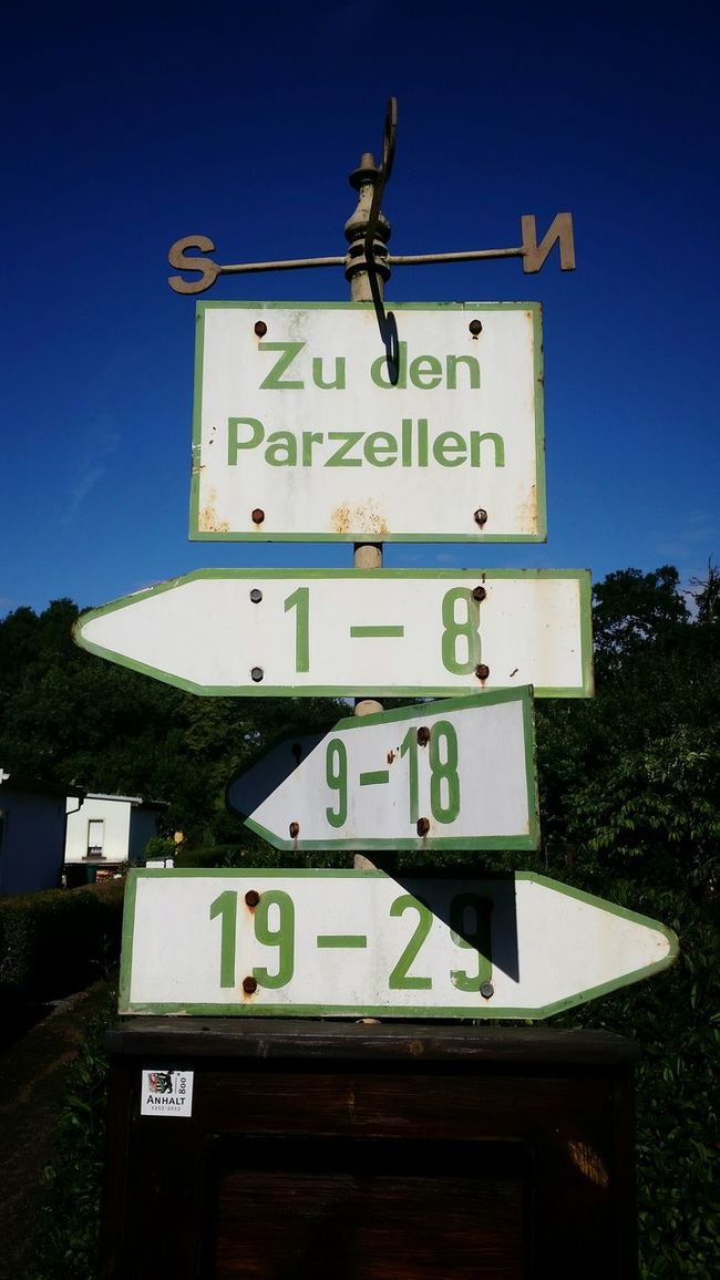 Wegweiser Signpost Guide Directional Sign Compass Sign Road Sign Blue Sky Garden Text German Kleingarten Kleingartenkolonie Kleingartenverein Sun Sunshine Day No People Close-up