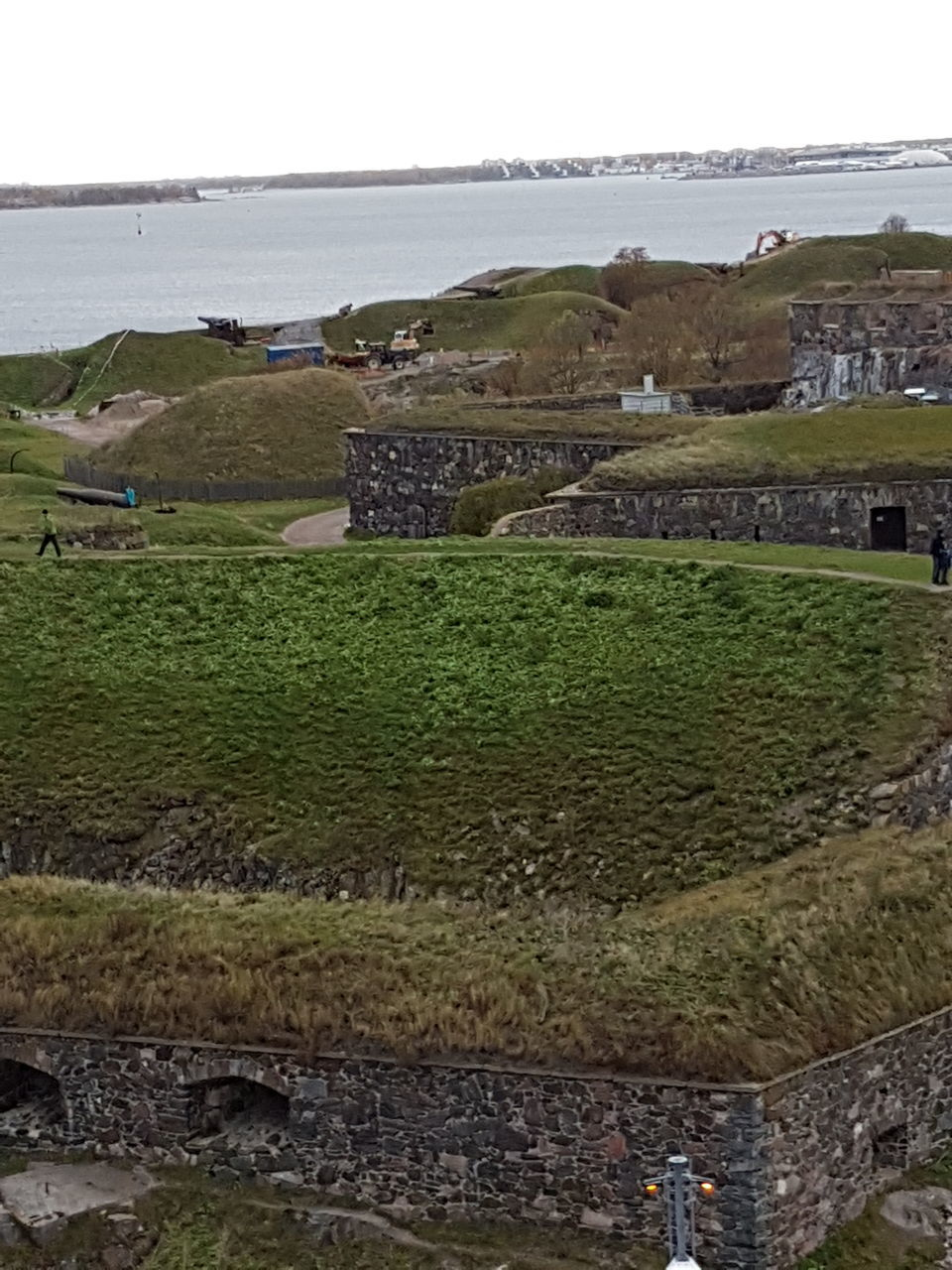 sea, water, history, nature, grass, horizon over water, day, ancient, outdoors, old ruin, no people, scenics, tranquil scene, green color, built structure, field, beauty in nature, travel destinations, tranquility, landscape, architecture, clear sky, sky, building exterior, ancient civilization