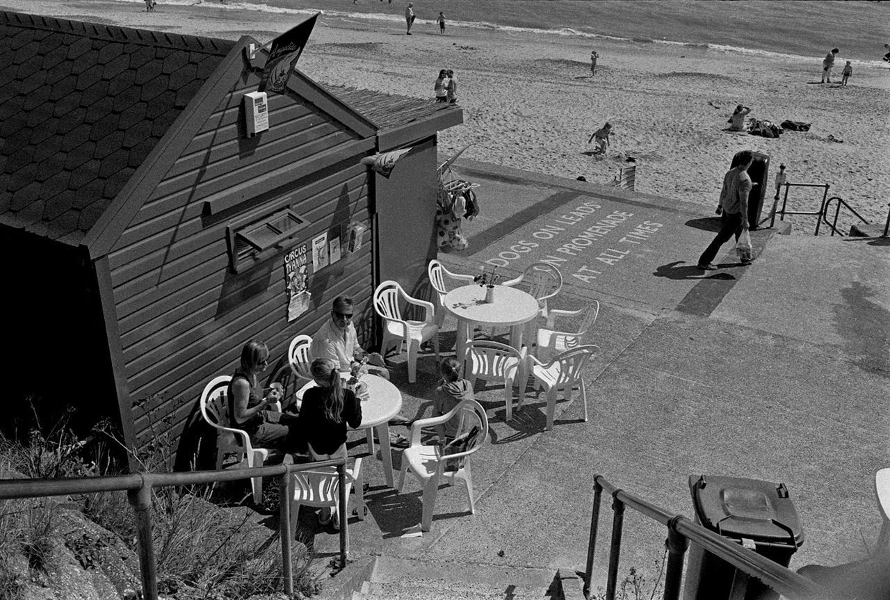The British on Holiday The British At The Seaside On Holiday Kids Children Two 2 Girls On Jetty Watch Dingy Deep In Thought Seaside Jetty Water Wake Dingy Orange Sand Coastline Suffolk Horizon Documentary Reportage Photography Taking Shots Colour Color Dresses From My Point Of  The British On Holiday By The Seaside Waves White Crest Foam Sea Ocean Beach Sand Bathing Trunks Crocks Thinking Deep Thoughts Contemplation Man Male White Pale Lonly Looking Figure Sad Sadness Documentary Reportage Photography Photograph Photographer Col
