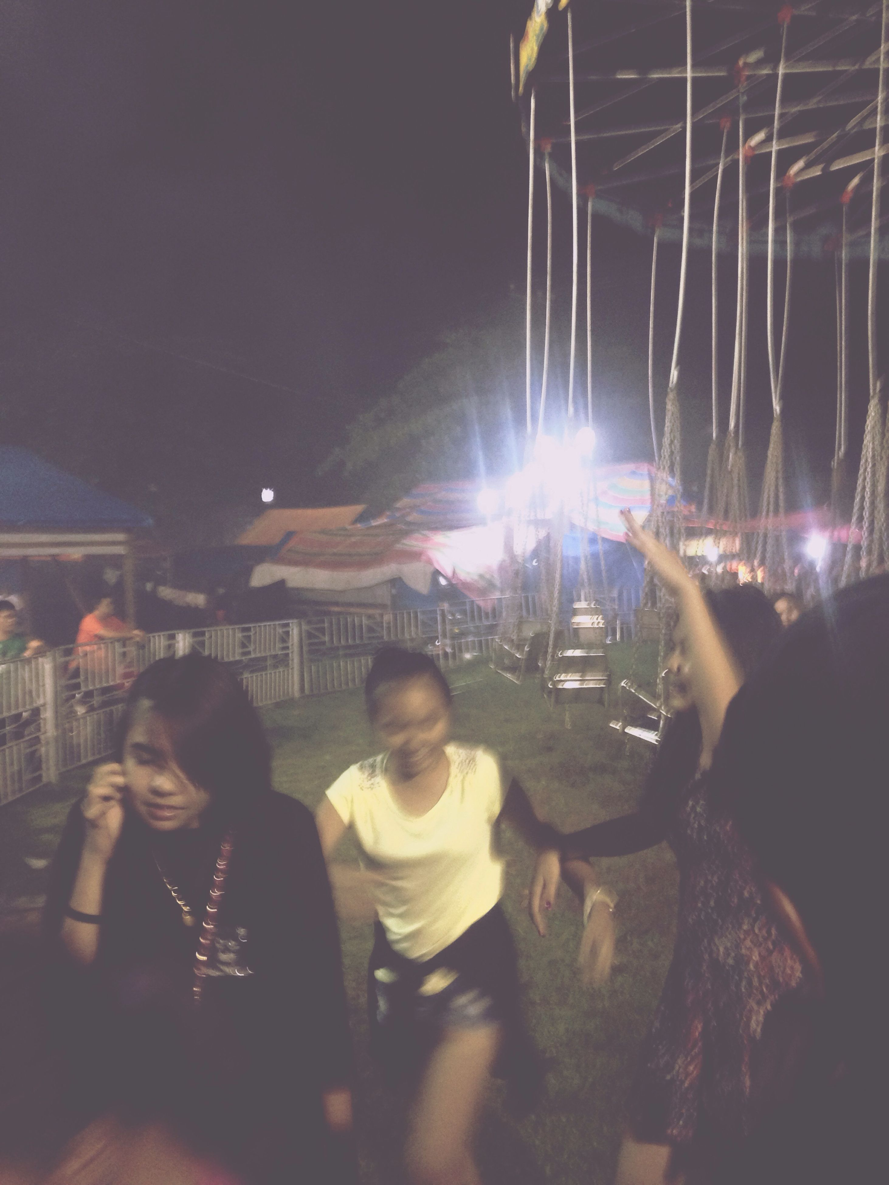 lifestyles, leisure activity, illuminated, togetherness, men, night, enjoyment, casual clothing, fun, sitting, arts culture and entertainment, standing, person, bonding, large group of people, lighting equipment, friendship