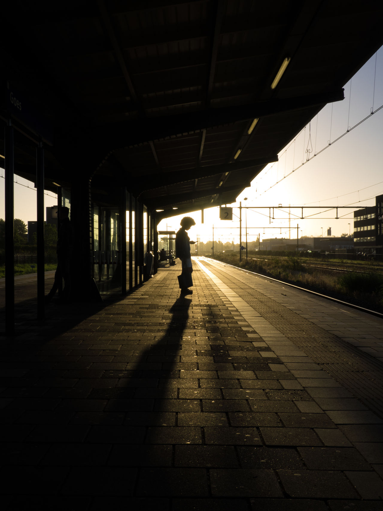 Adult Adults Only Commute Copy Space Day Full Length Morning One Person People Person Perspective Platform Real People Silhouette Station Sunrise The City Light Unrecognizable Person Waiting Woman