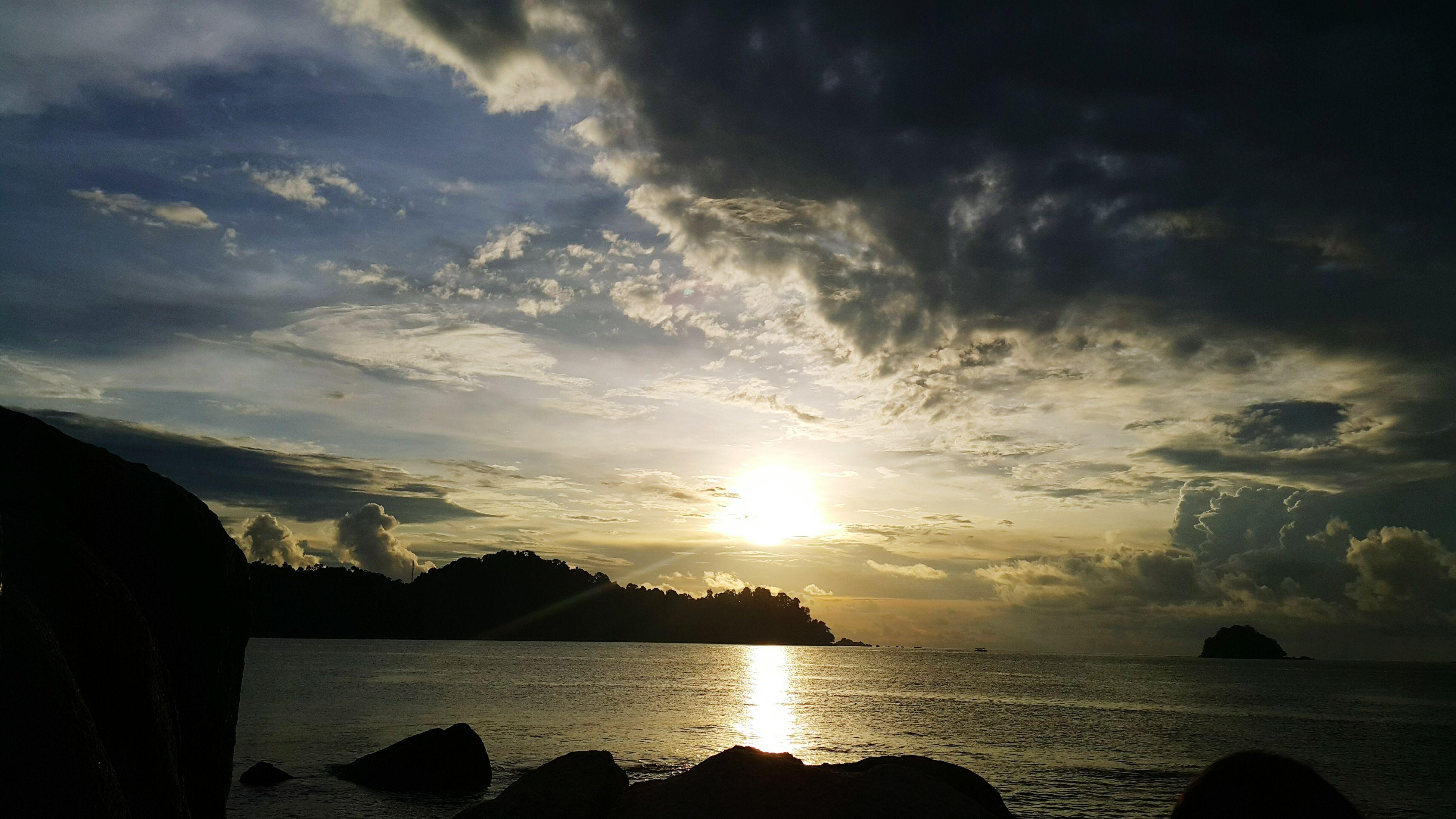 water, sky, sun, scenics, beauty in nature, tranquil scene, tranquility, cloud - sky, sunset, silhouette, sea, sunbeam, nature, mountain, sunlight, idyllic, cloud, reflection, cloudy, lake