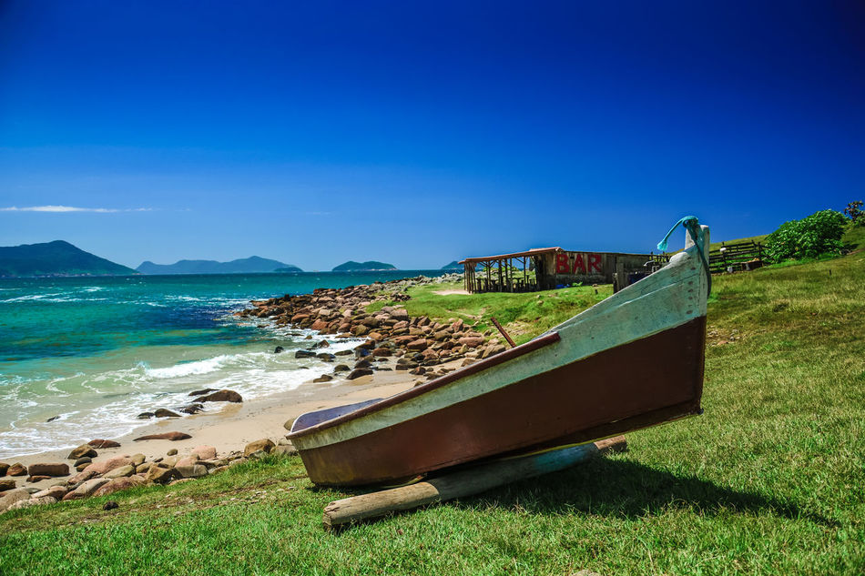 Abandoned Beach Beauty In Nature Blue Clear Sky Damaged Day Grass Mountain Nature Nautical Vessel No People Outdoors Run-down Scenics Sea Sky Tranquil Scene Tranquility Transportation Water
