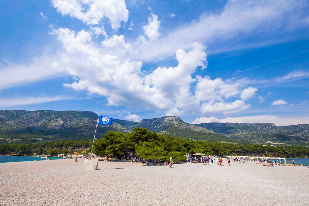 beach, sand, cloud - sky, nature, mountain, sky, beauty in nature, scenics, day, tranquil scene, tranquility, blue, outdoors, vacations, large group of people, water, real people, sea, beach volleyball, people