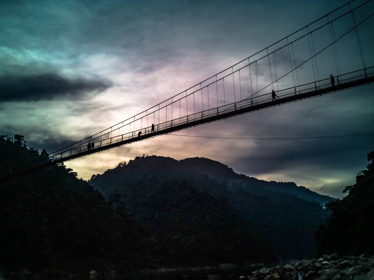 connection, cloud - sky, sky, mountain, bridge - man made structure, outdoors, suspension bridge, no people, nature, architecture, built structure, mountain range, cable, scenics, low angle view, beauty in nature, tranquility, day, bridge, travel destinations, tree, storm cloud