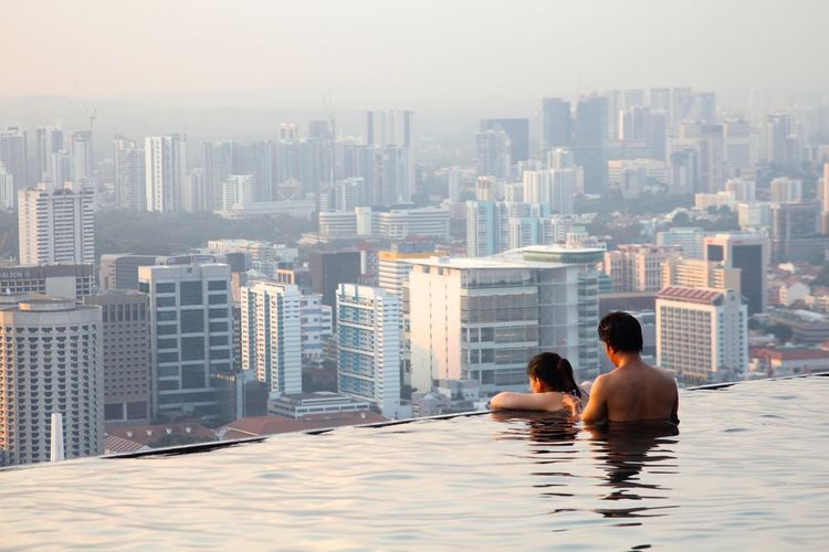 Architecture City Cityscape Day Infinity Pool Marina Marina Bay Sands Modern Outdoors People Pool Rear View Relaxation Singapore Singapore View Sky Skyscraper Togetherness Tourist Travel Destinations Two People Urban Skyline Vacations Water