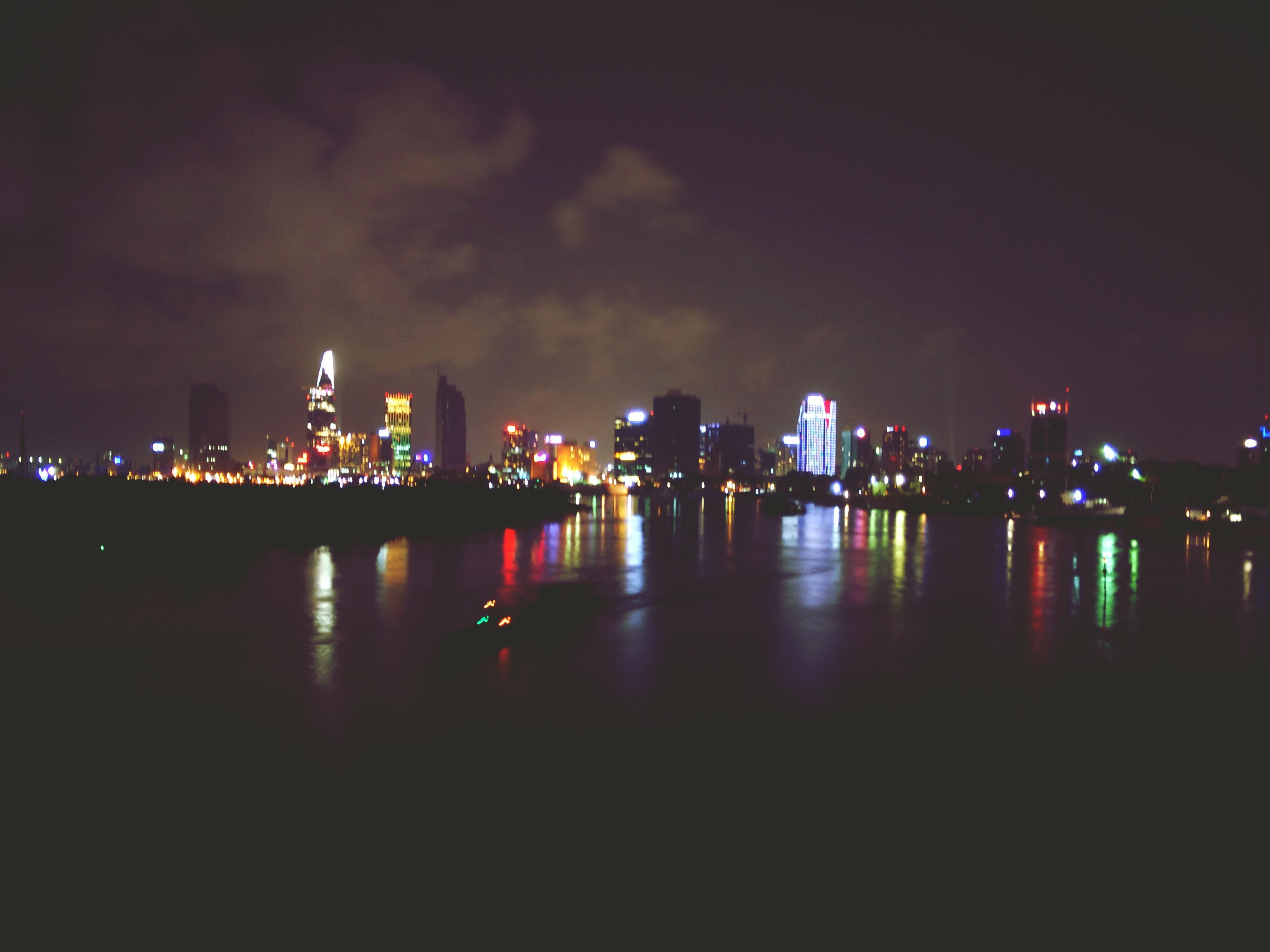 illuminated, night, water, building exterior, architecture, city, built structure, reflection, waterfront, river, cityscape, sky, sea, mid distance, lighting equipment, skyscraper, copy space, urban skyline, city life, dark