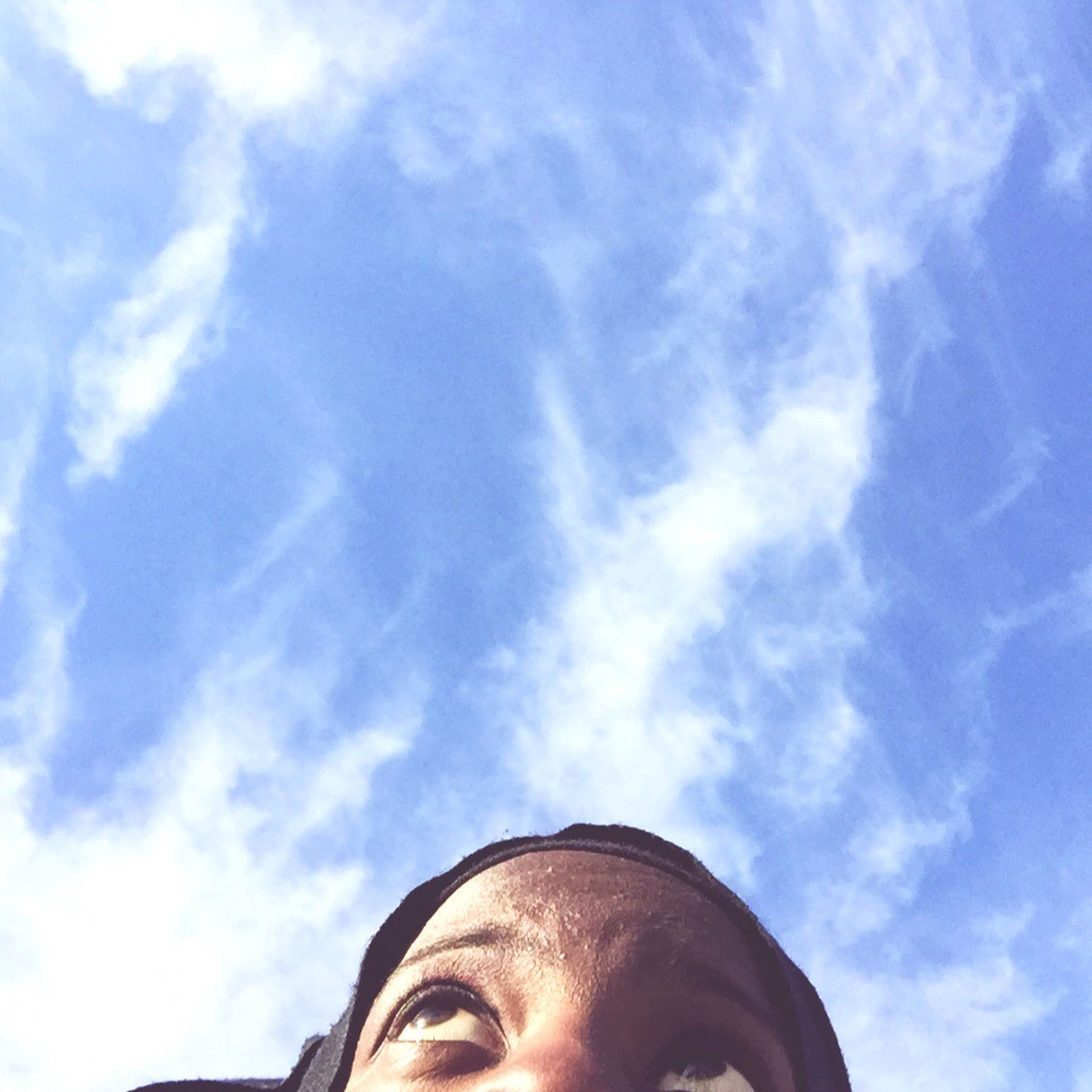low angle view, sky, headshot, lifestyles, blue, leisure activity, cloud - sky, head and shoulders, day, part of, cloud, young adult, outdoors, close-up, person, sunlight, looking at camera